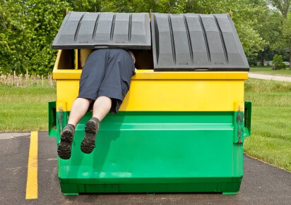 Dumpster with 2 legs sticking out