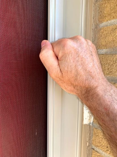 A closed fist knocking on a light brown framed screen door in front of a red door.