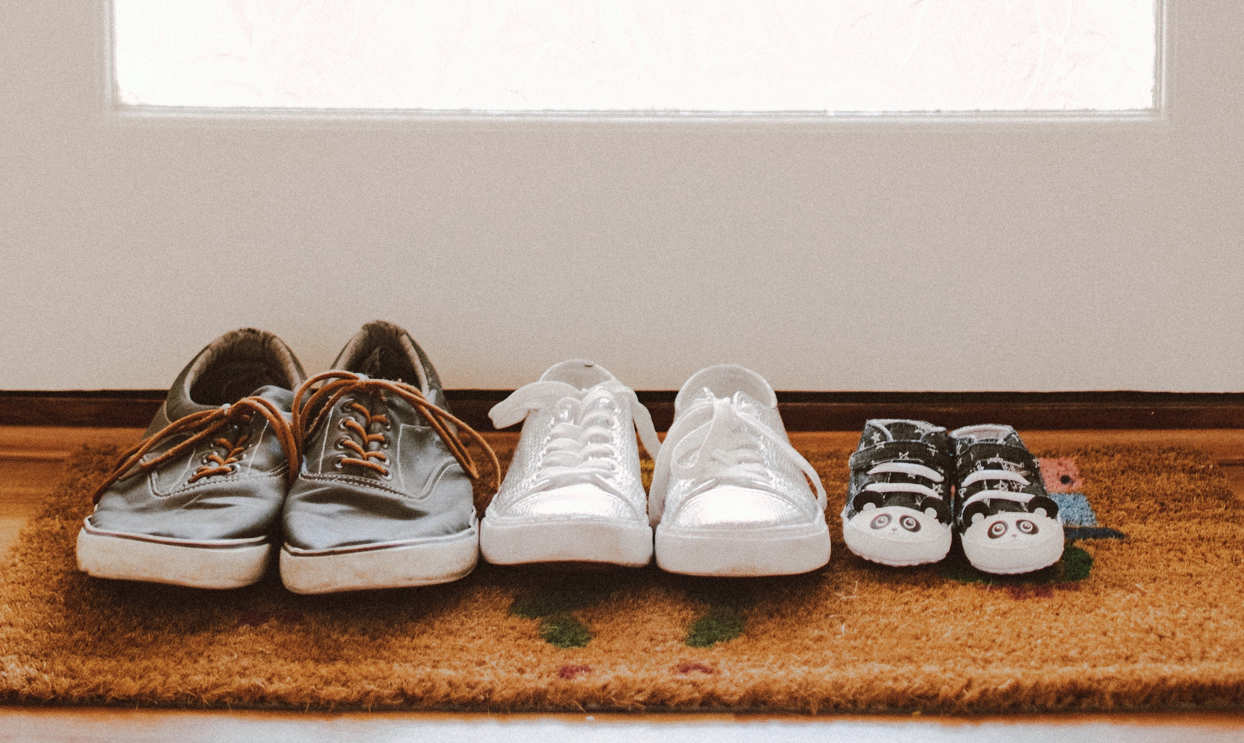 Three pairs of used shoes in different sizes and styles sit on a matt.