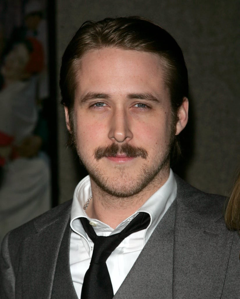 Ryan Gosling in a grey suit when he had a thick mustache