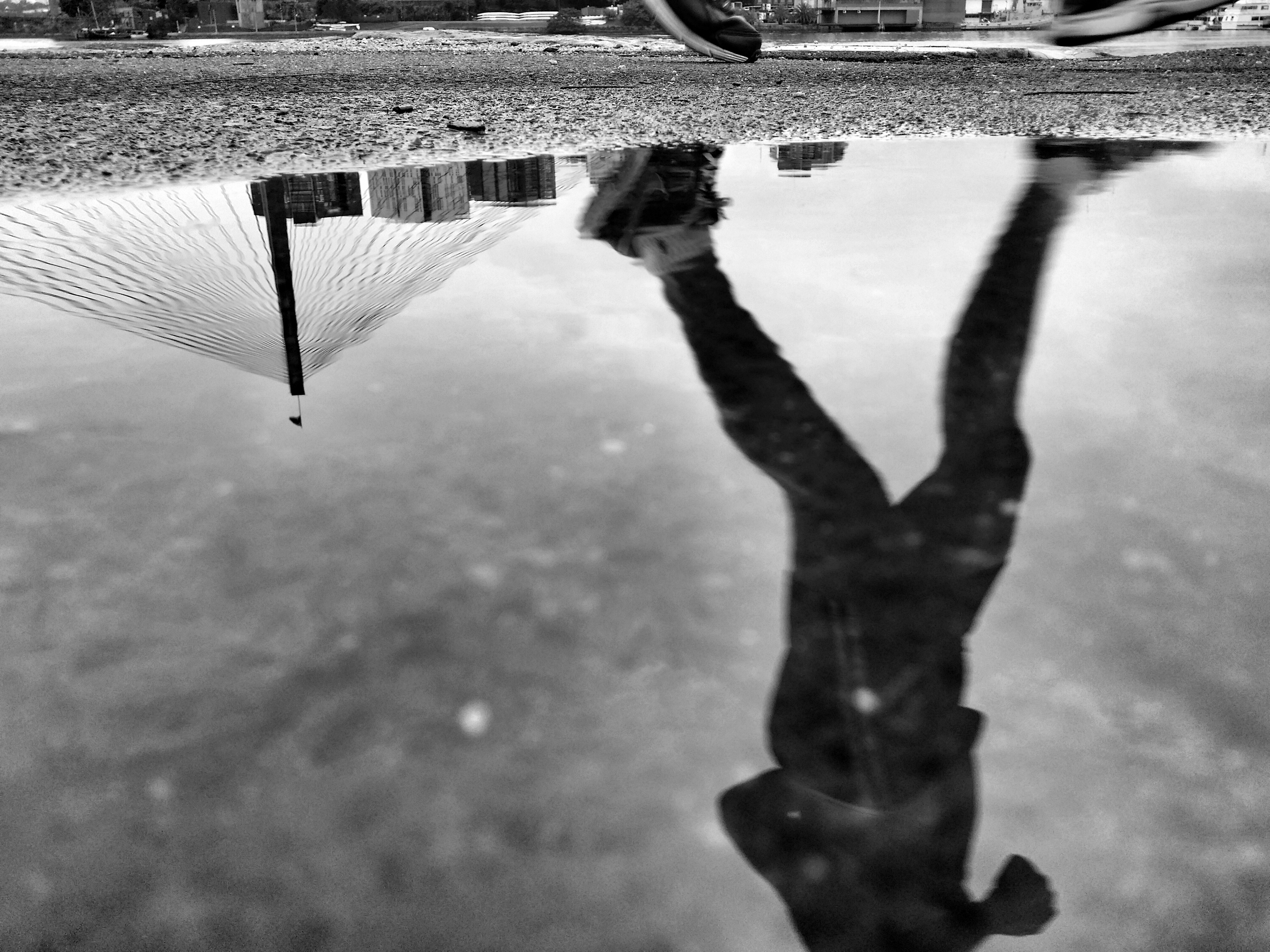 A runner outside reflected in a puddle.