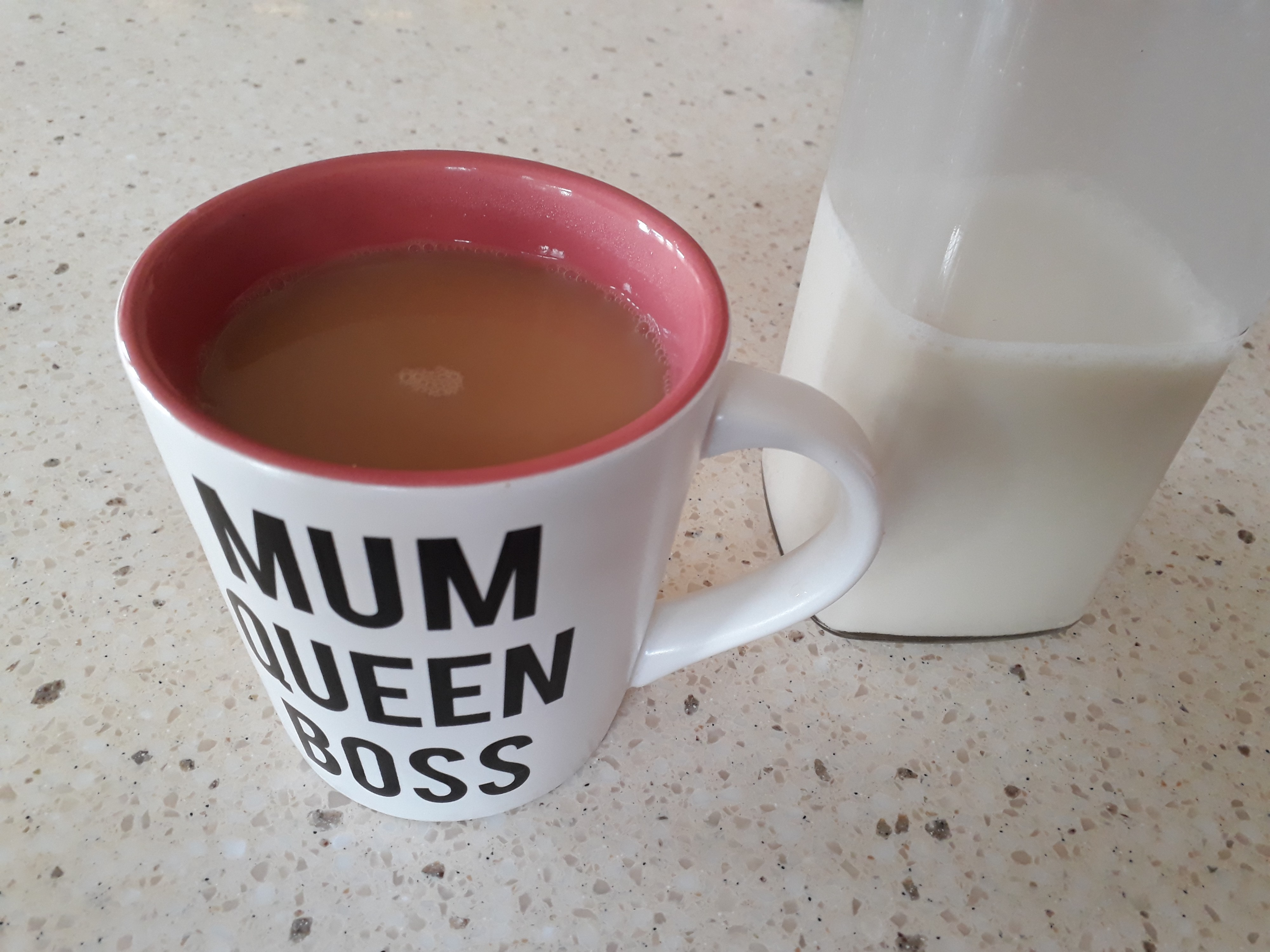 mug of tea with the words mum, queen,  boss, and a bottle of oat milk