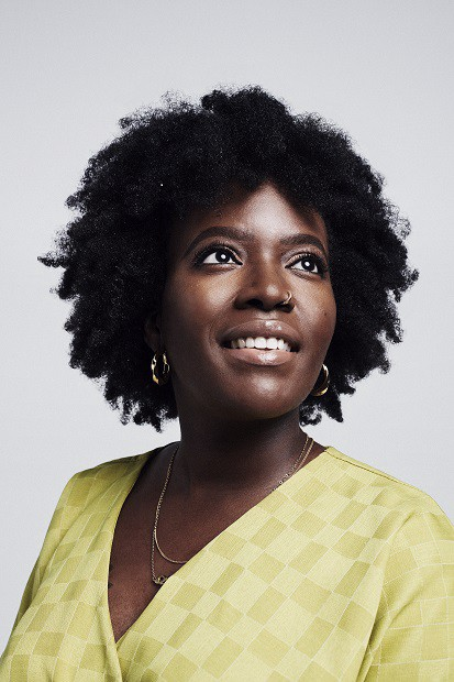An image of Seyi Akiwowo, founder and Director at Glitch and author of this article. She's wearing a yelow top and gold earrings. She's looking up and to the right side, and is smiling.