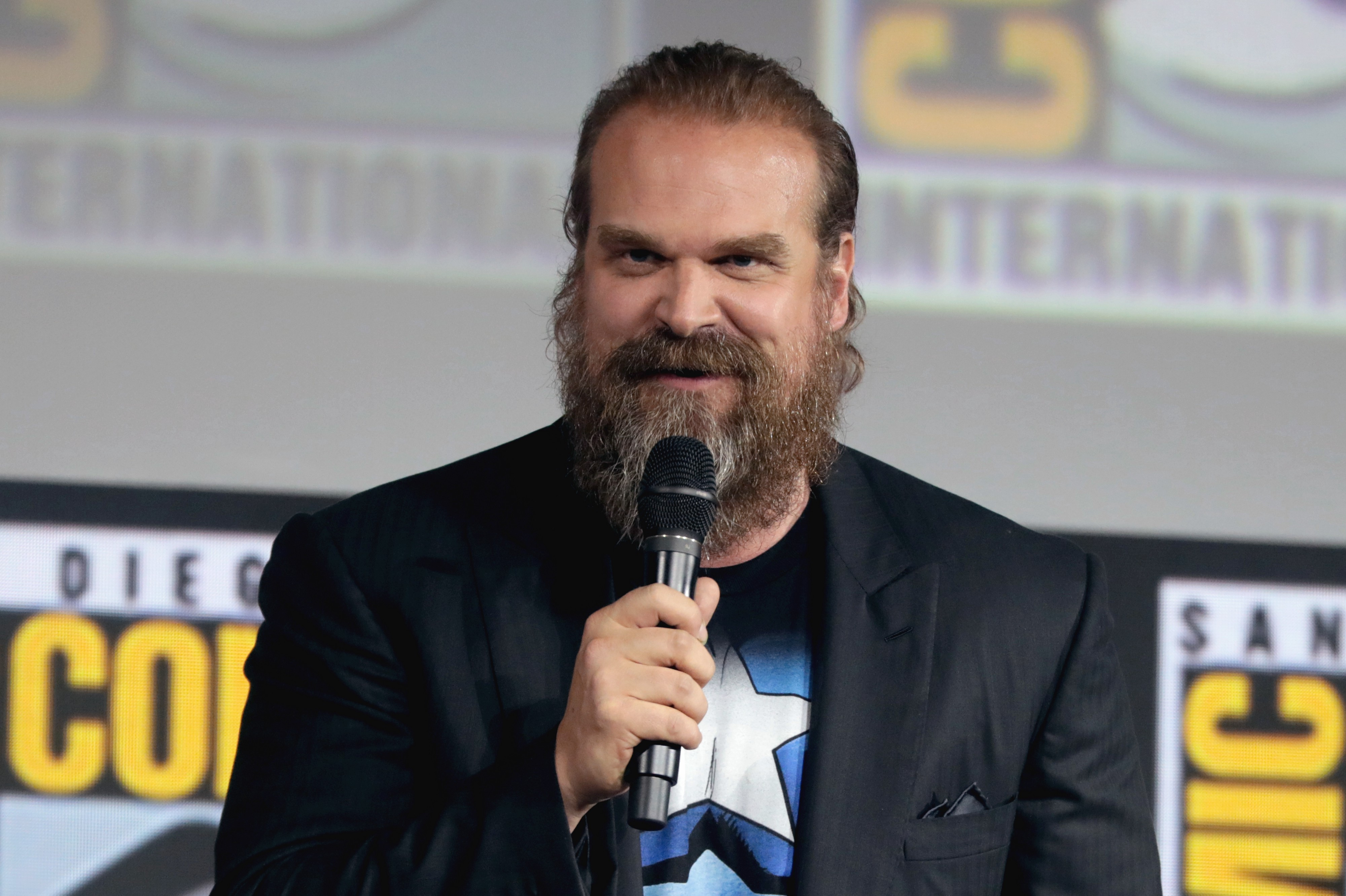 David Harbour holds a microphone.