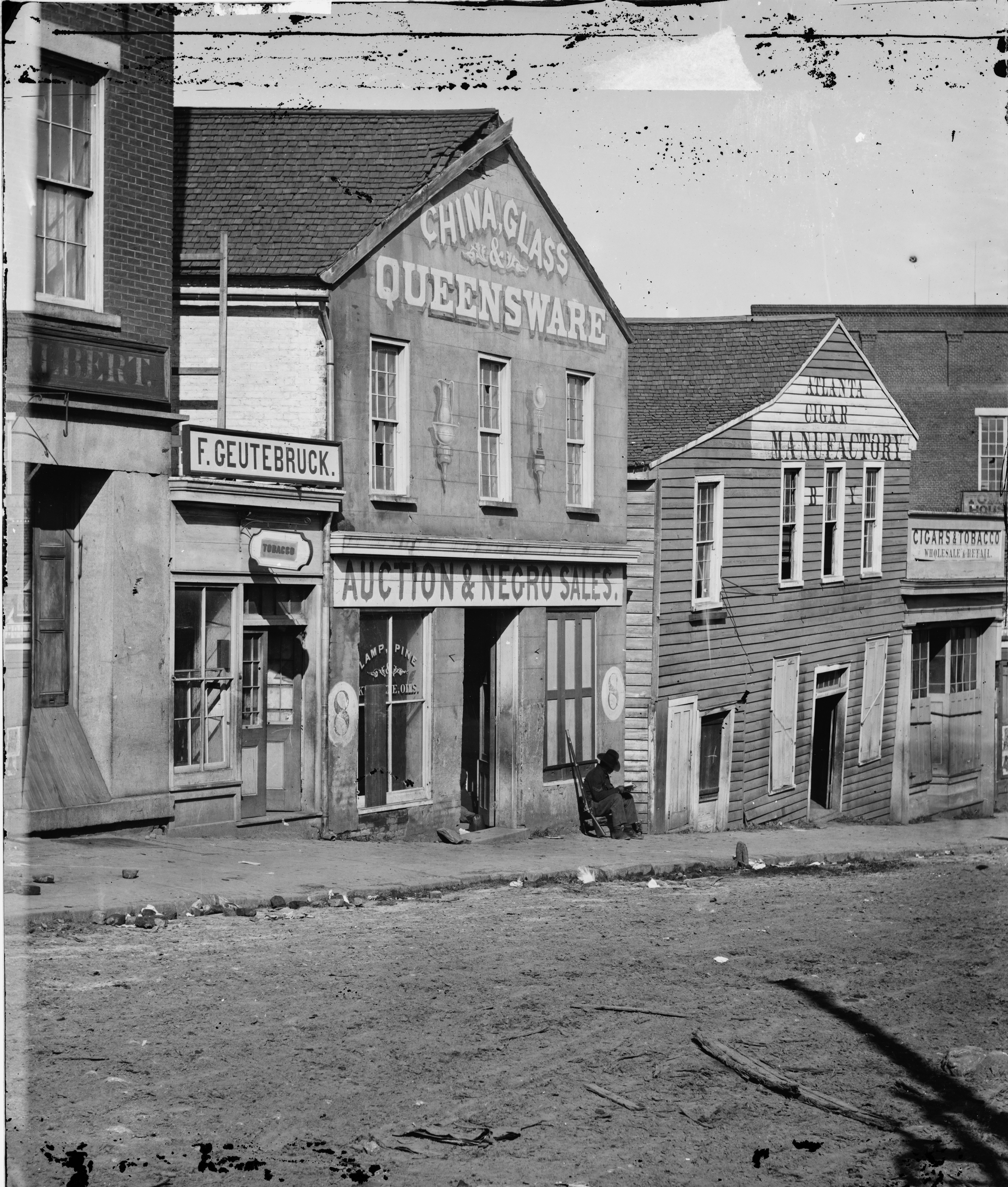 """Black and white photograph of a street in Atlanta in 1864 featuring a building with a sign reading """"Auction & Negro Sales."""""""