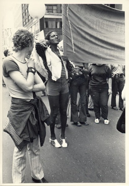 A black and white photo of Marsha P. Johnson at a protest, holding one side of a banner proudly. She is smiling and standing up tall to hold the banner high.