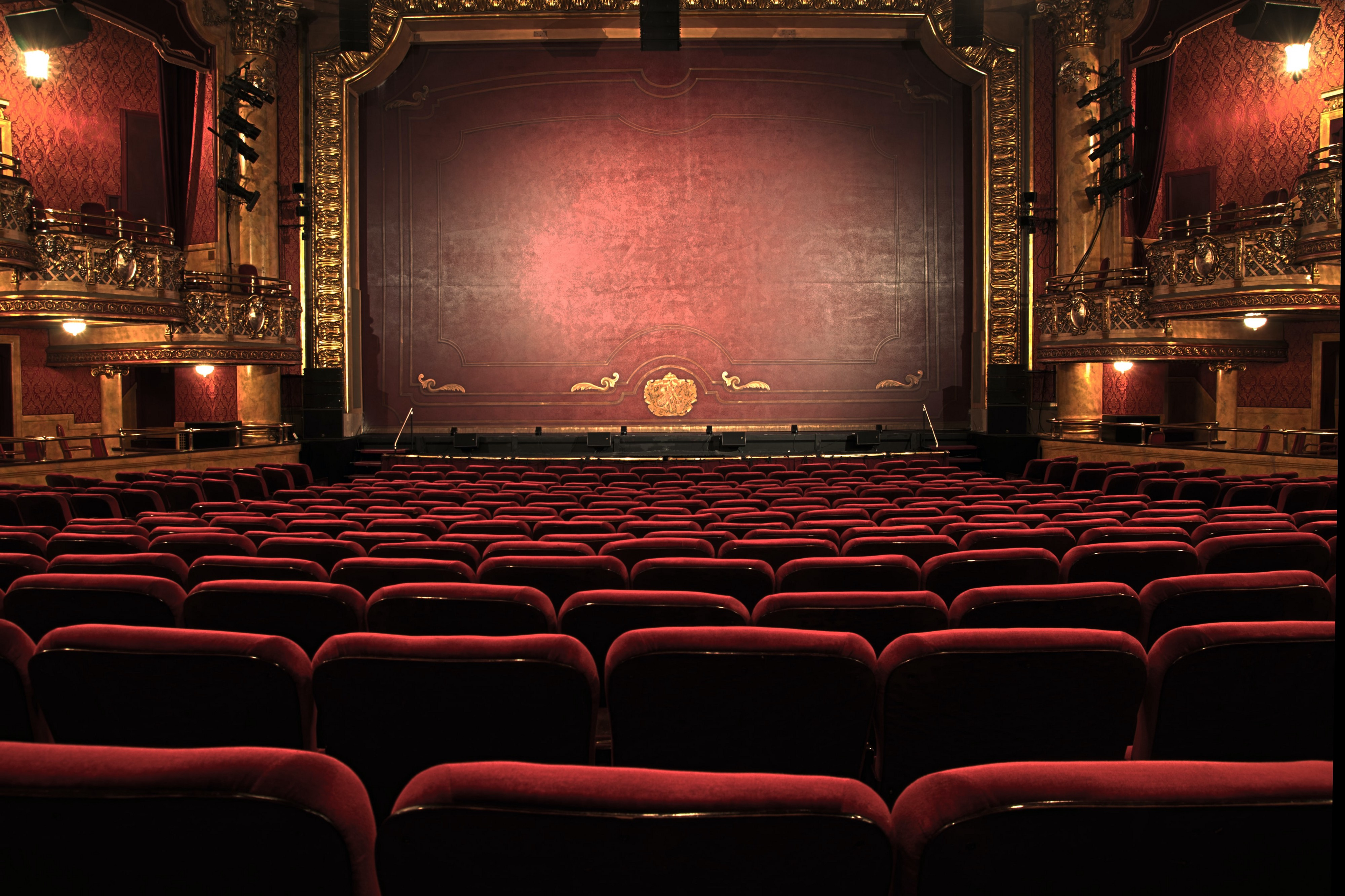 A dark red theatre with a big golden stage