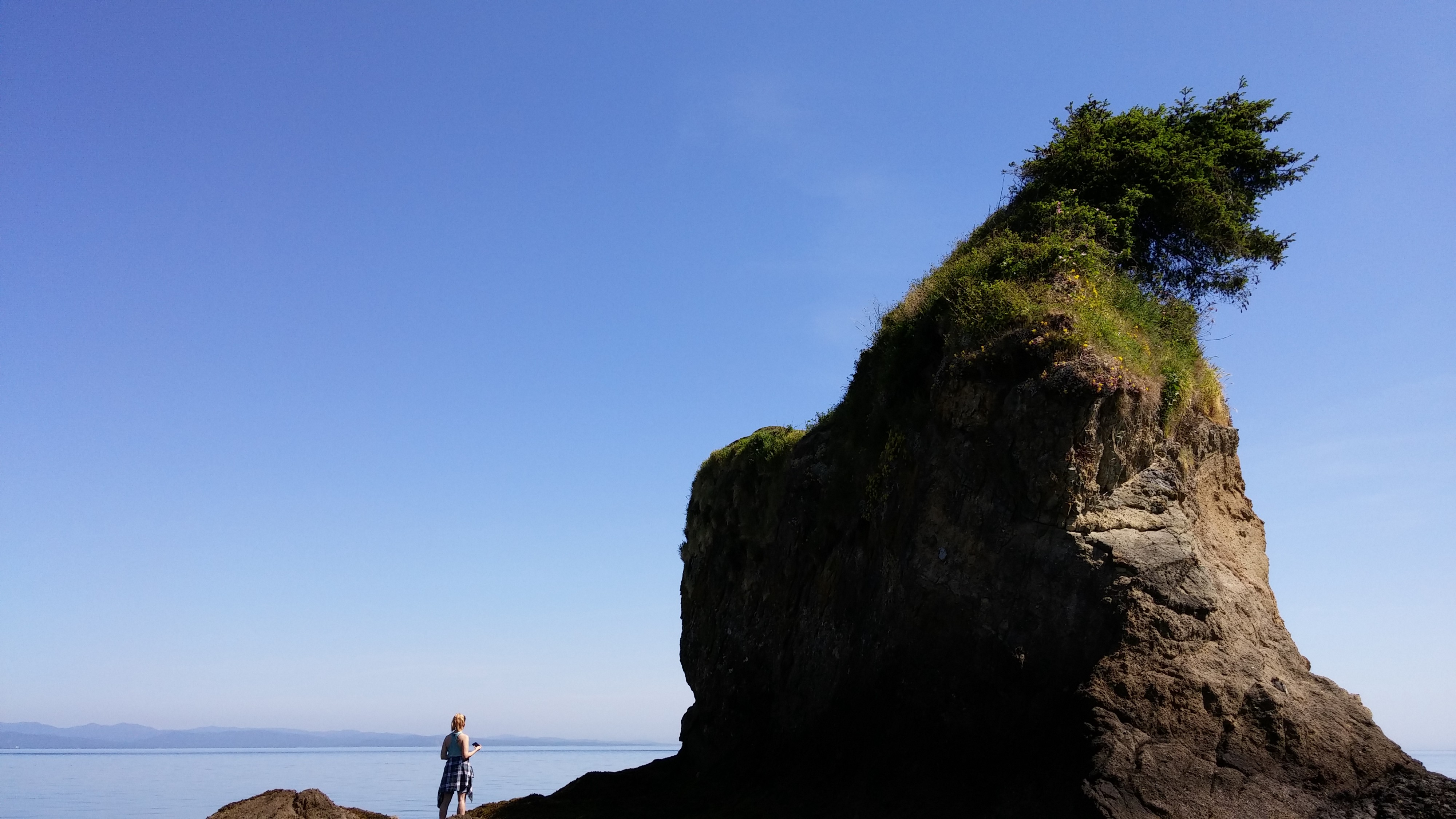 A hiker appears tiny in comparison to the sea stack she is standing next to.
