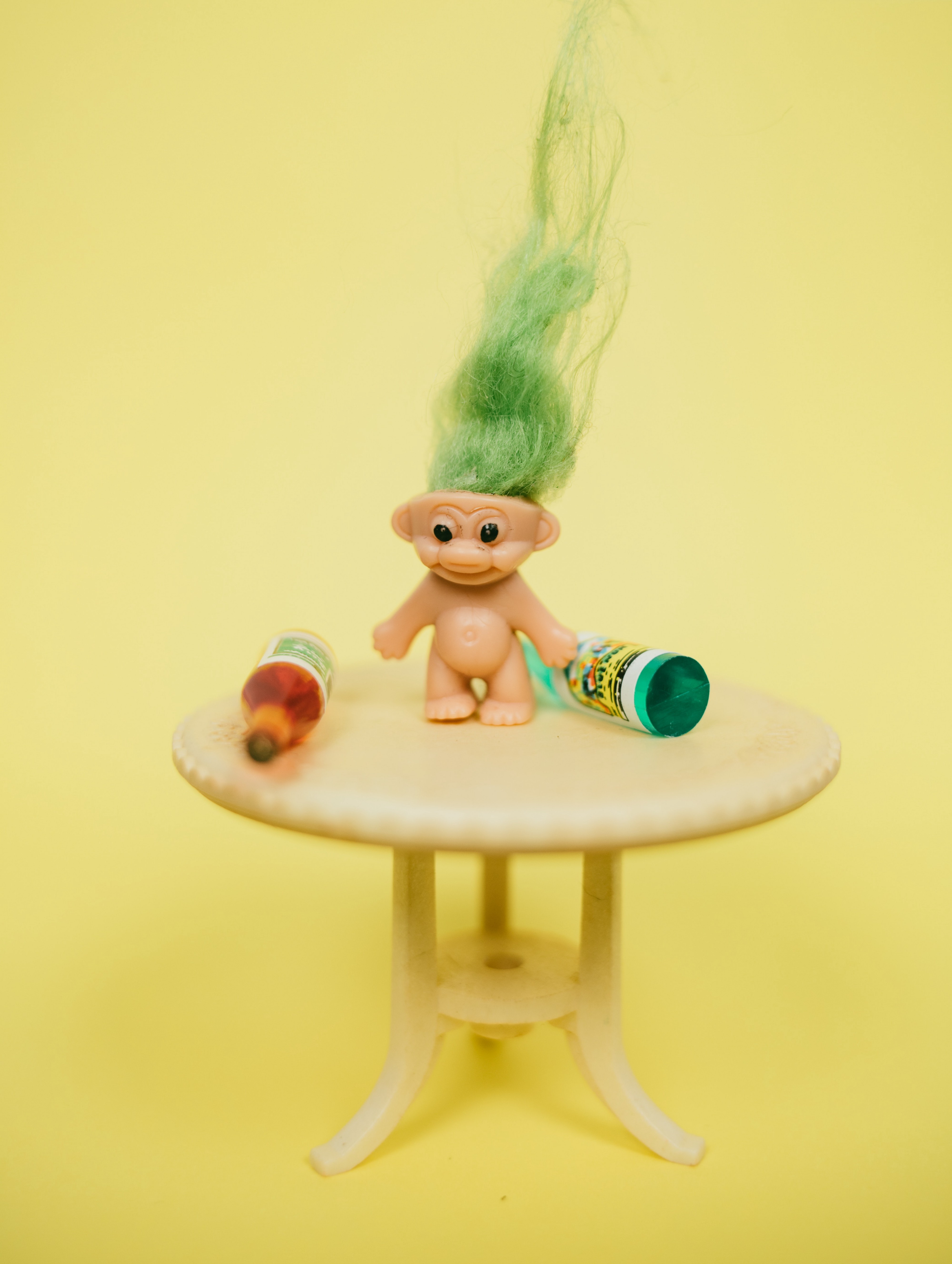 A strange picture with a toy troll in between two bottles while standing on a piece of furniture