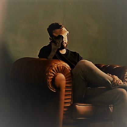 Man in a chair with his hand over his face.