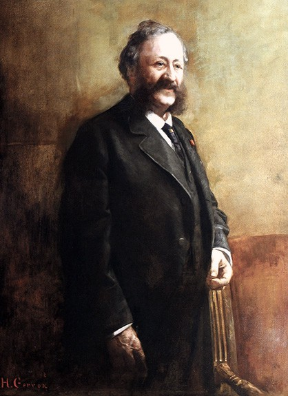 Evans as an older man, wearing a black suit. He still his those enormous mutton-chop whiskers.