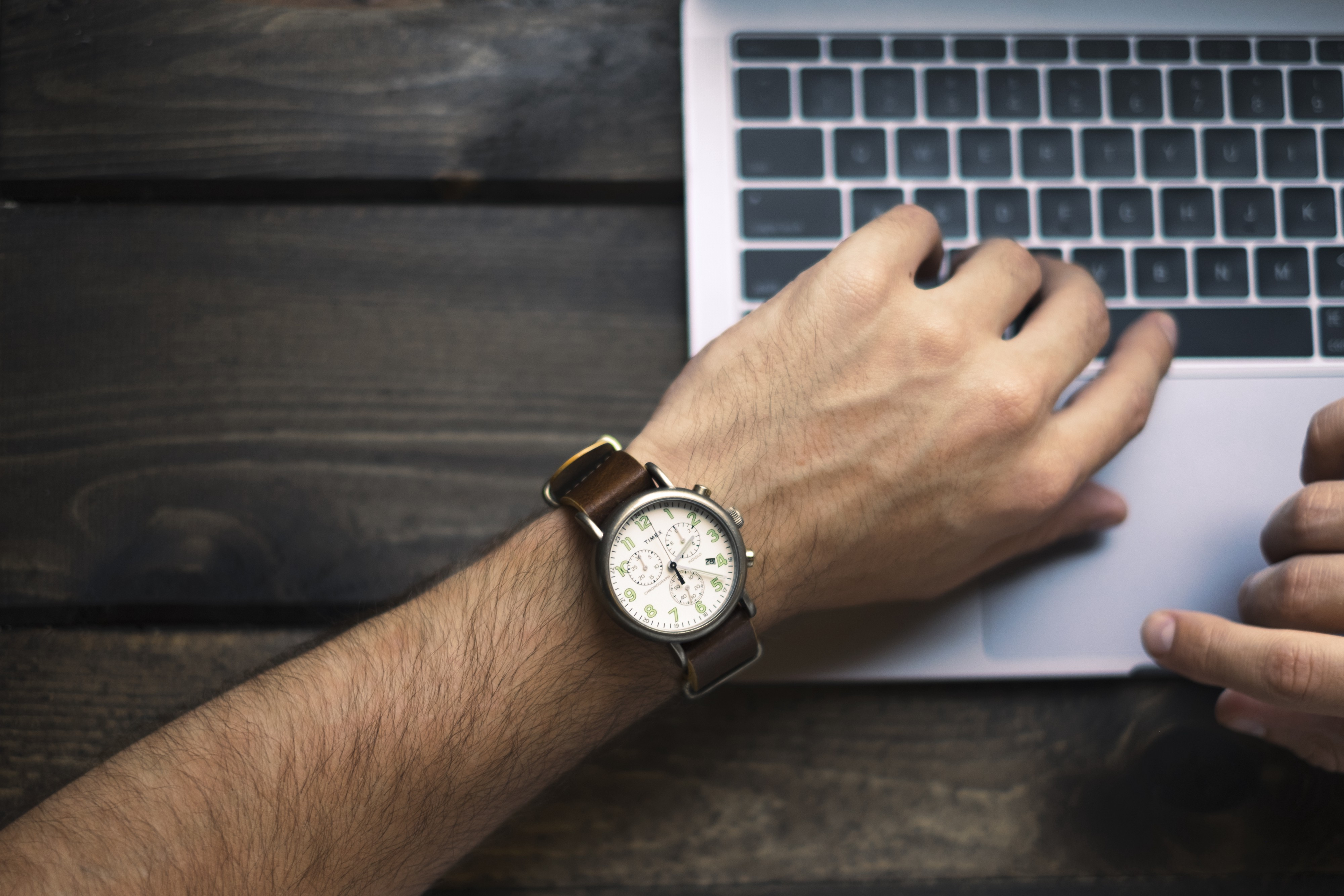 A busy entrepreneur checks his watch at his computer. He is busy with his task.