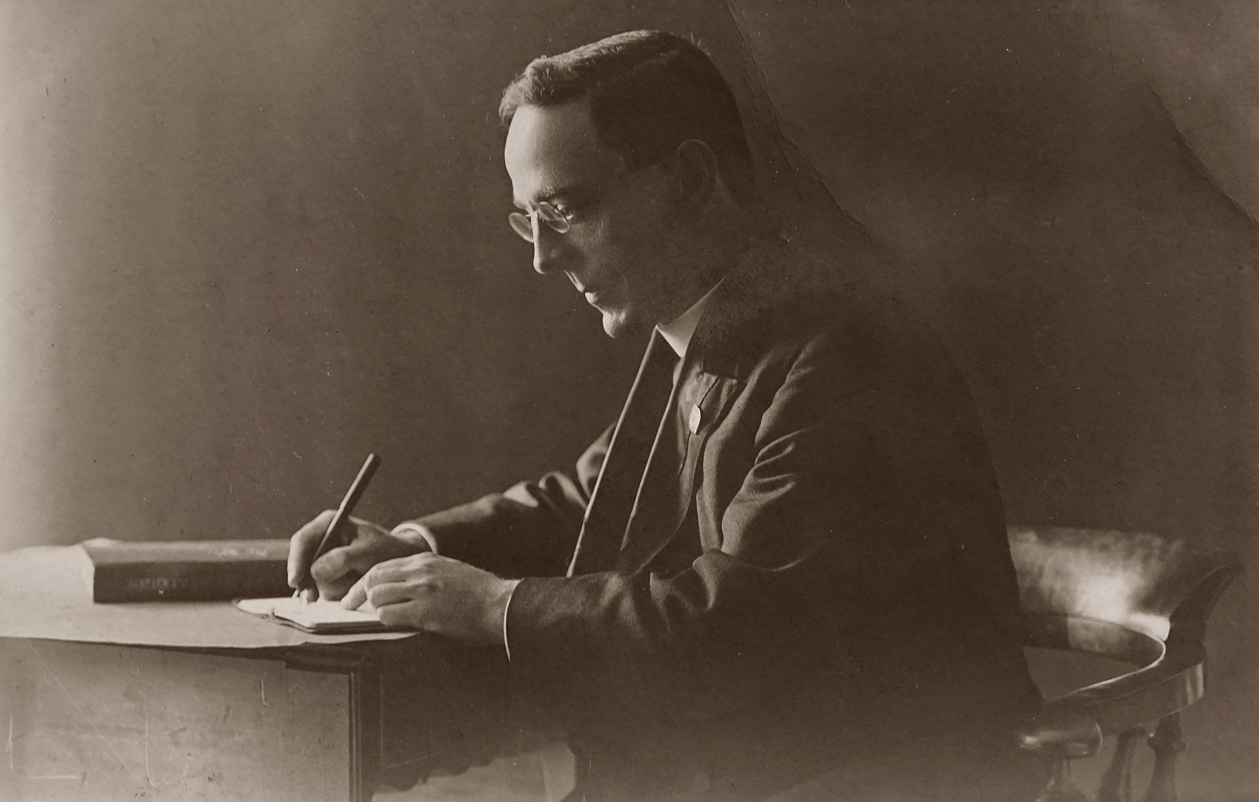 Black and white, old photo of a man's side profile, writing a letter