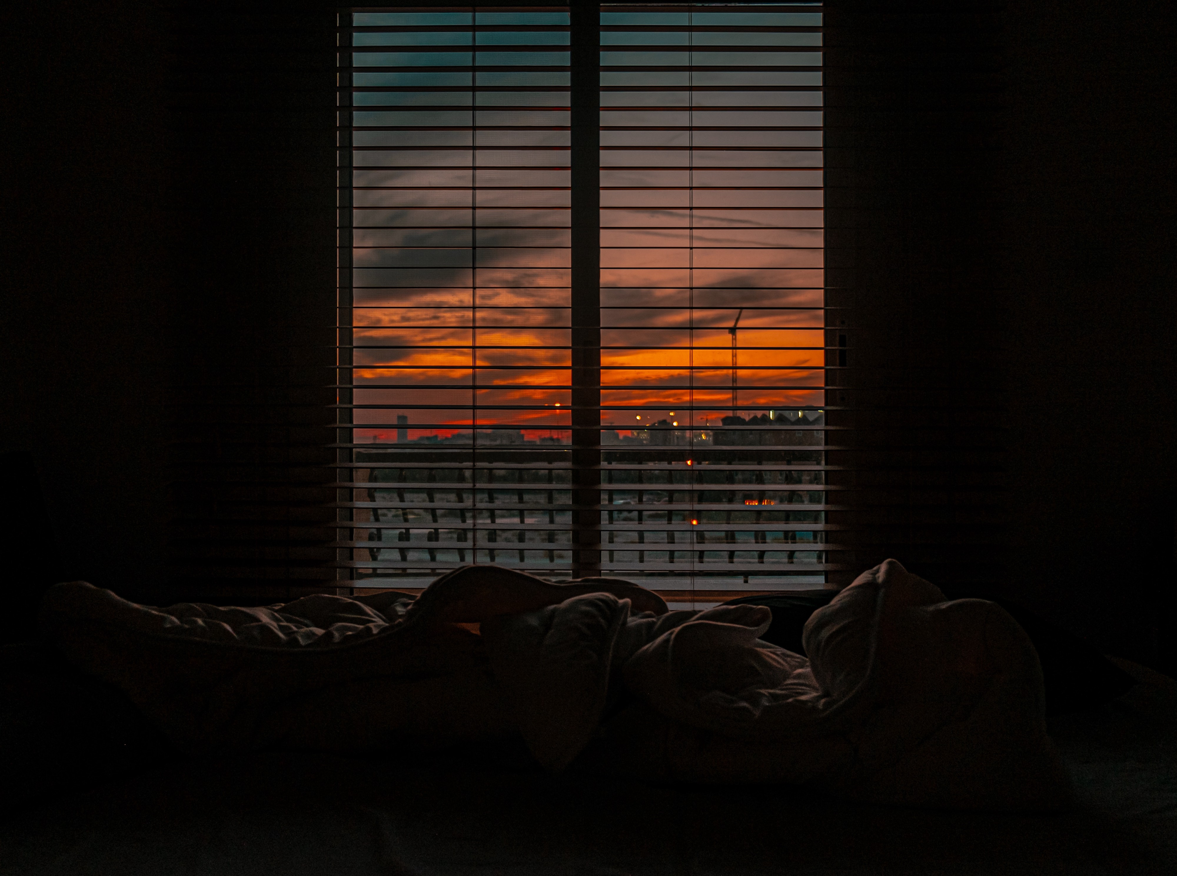 crumpled-blanket-in-dark-room-at-sunset