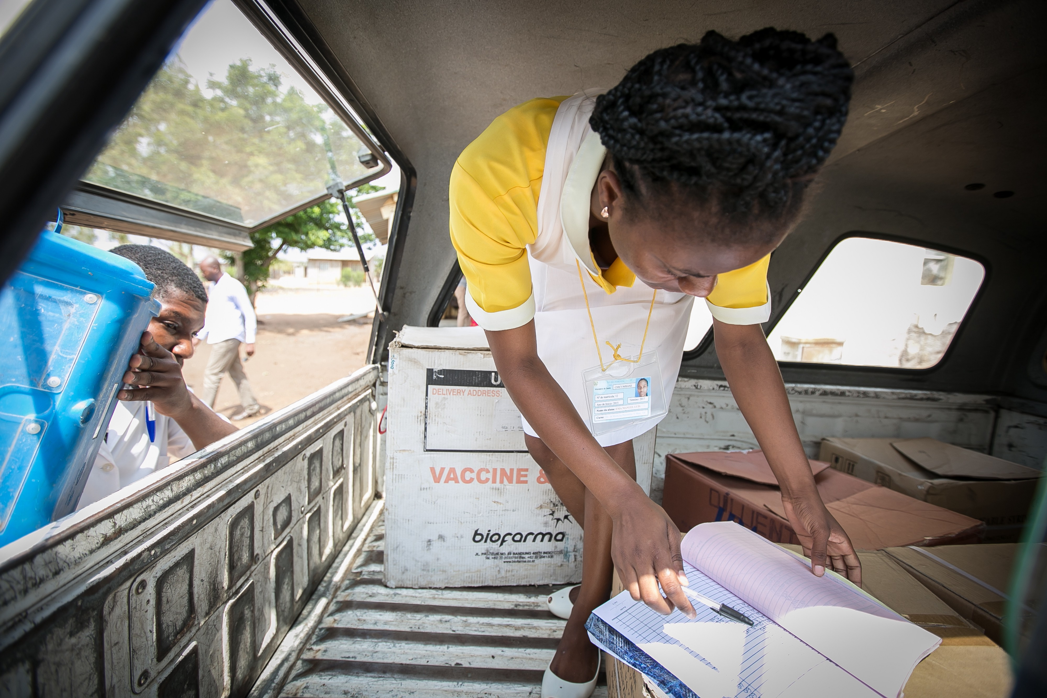 A pharmacy assistant in Mozambique reviews a vaccine delivery to a health center. Credit: Paul Joseph Brown