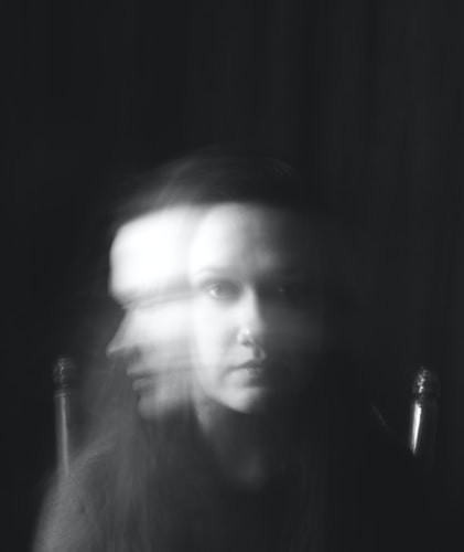 A black and white photo of a woman staring at the camera and on her right side there is an after-image-blur of her looking to the side