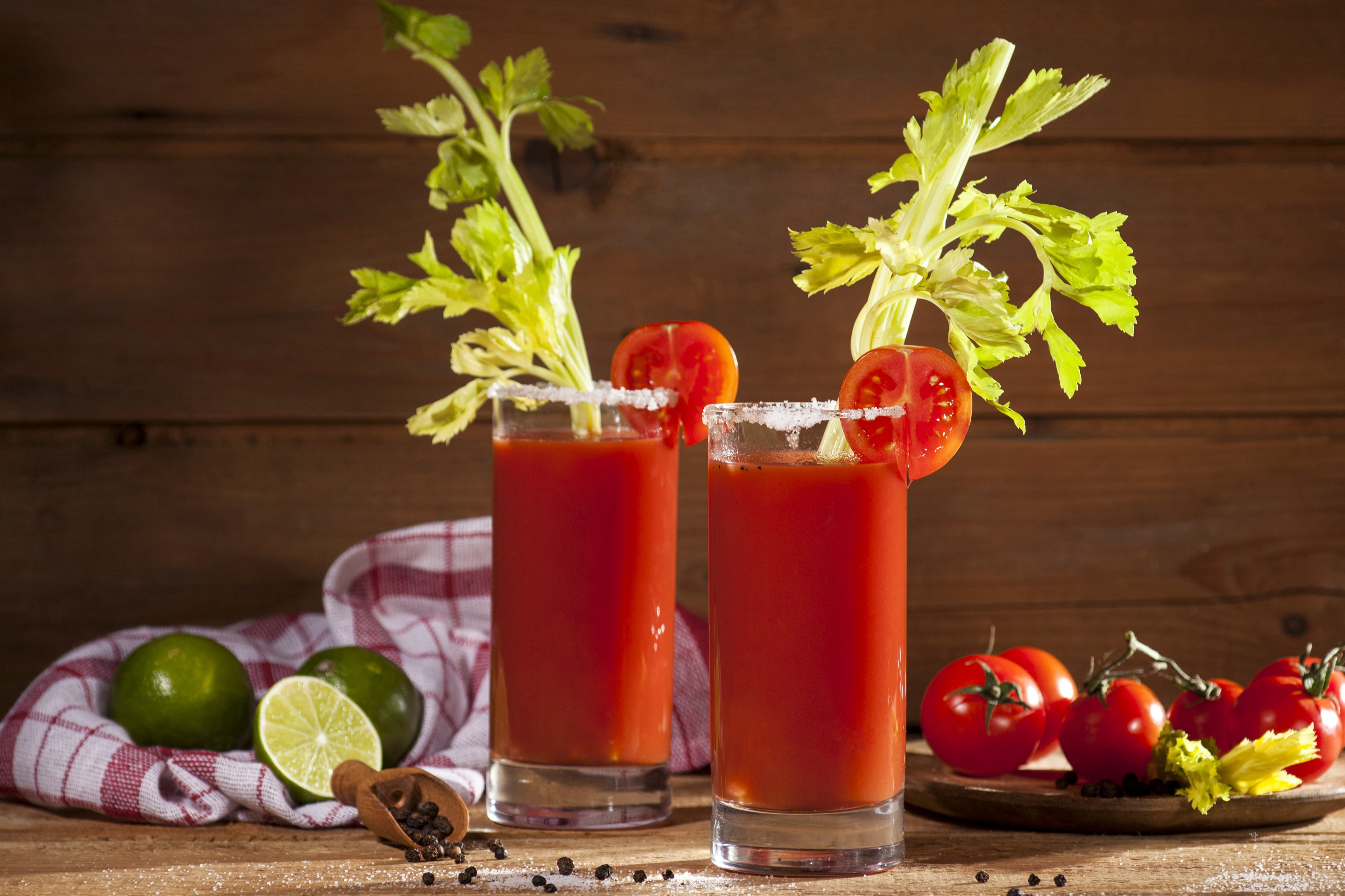 Two tall glasses filled with Bloody Mary mix and garnished with celery sticks and tomatoes.