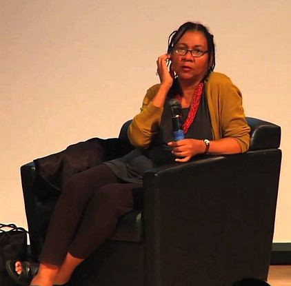 bell hooks in an armchair with a microphone
