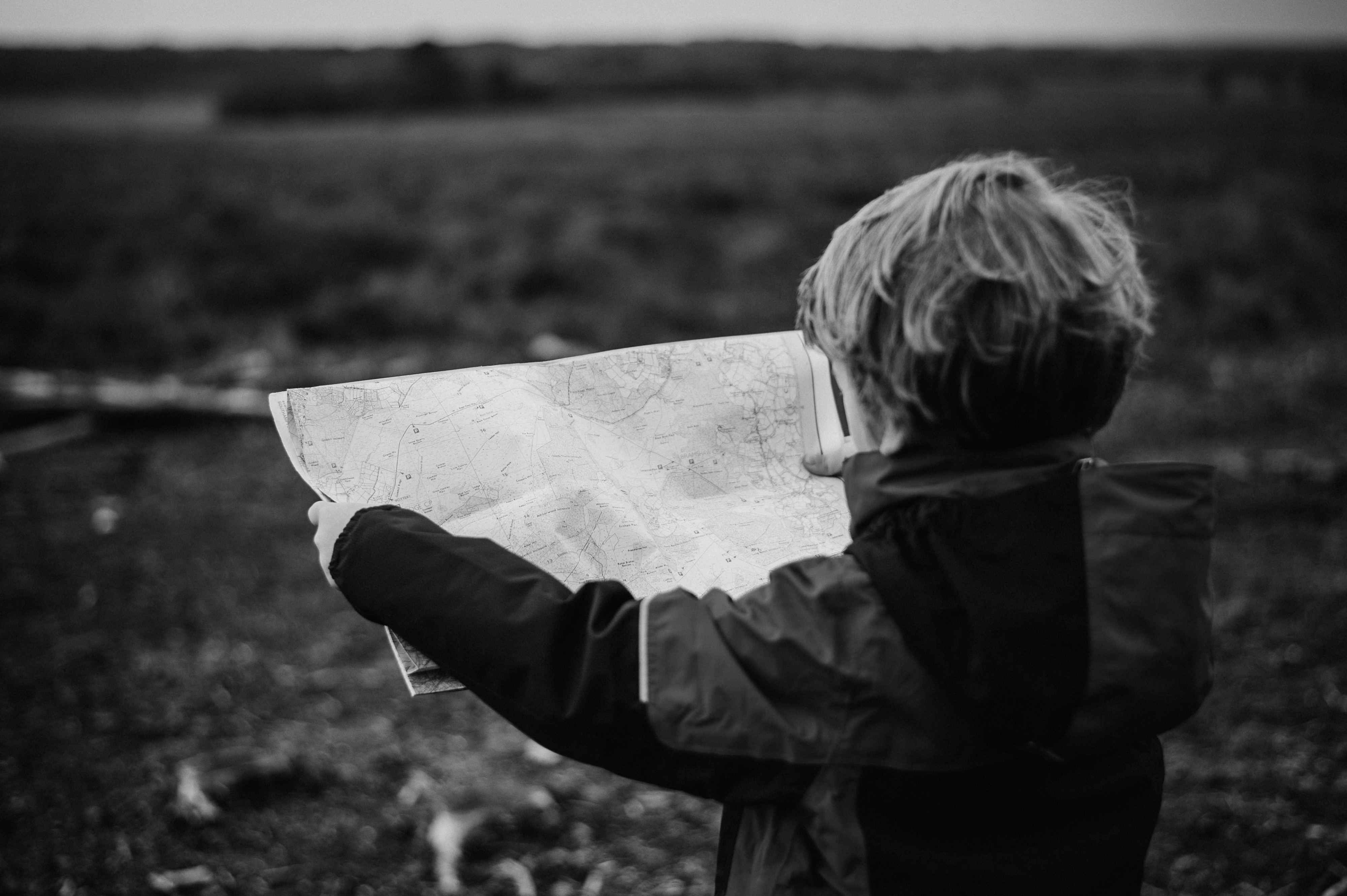 Child looking at map facing an open field.