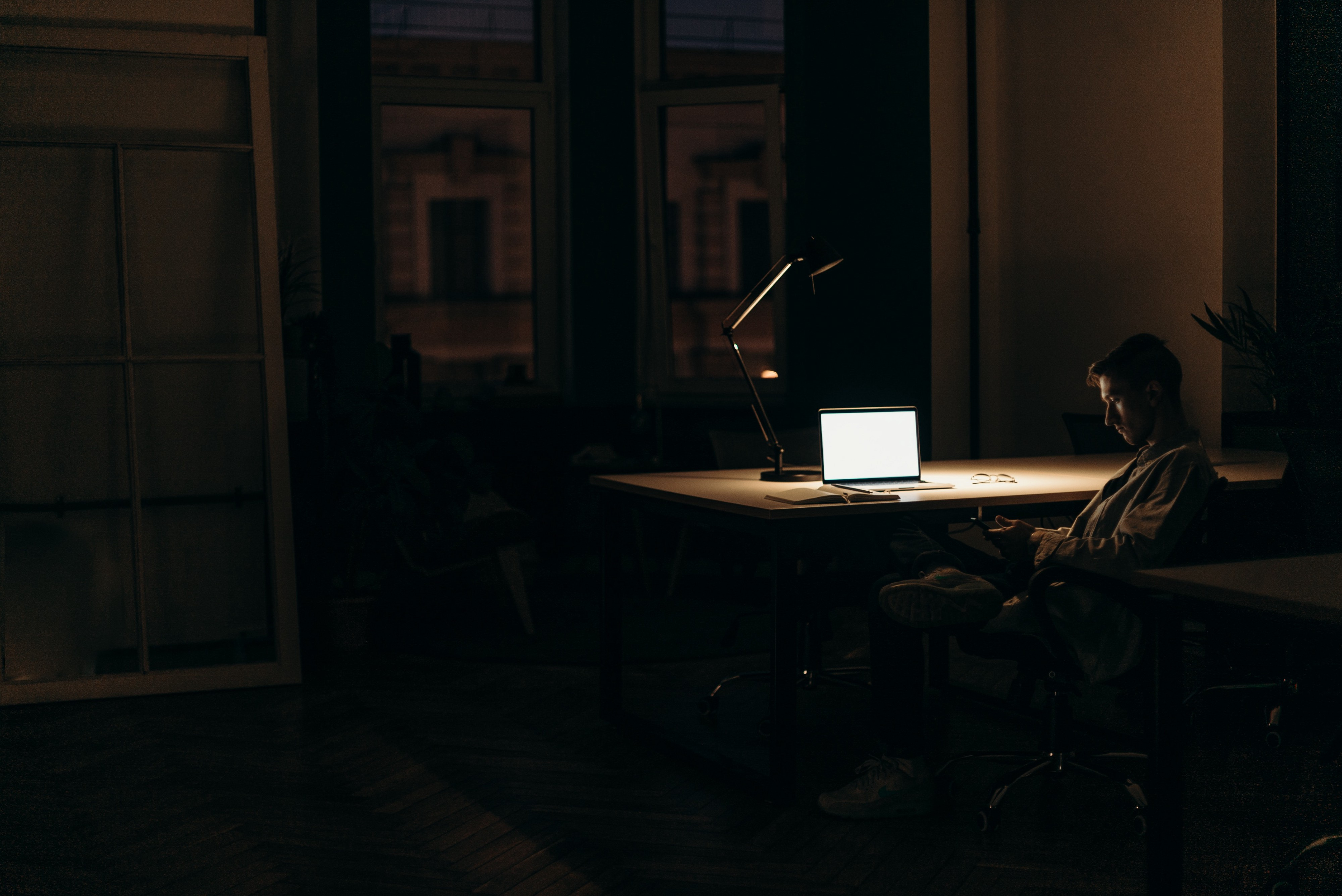 A man sits in the dark; his devices his only sources of comfort. The loneliness shrouds him together with the darkness.