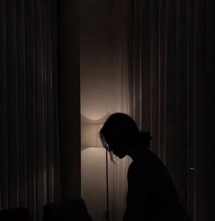 A sad girl in a dark room, sitting by the side of a table lamp.