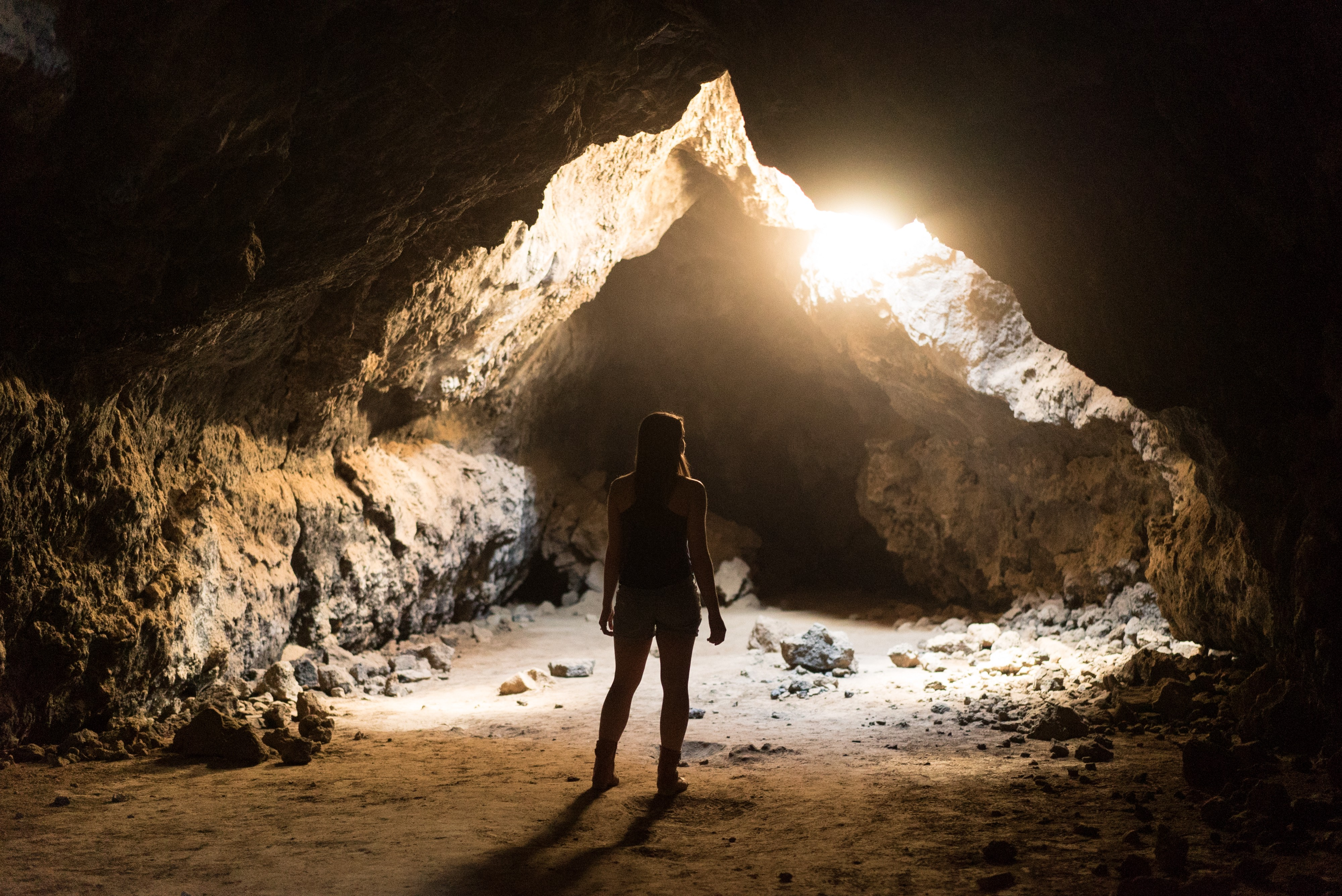 Girl looking outside of a cave.