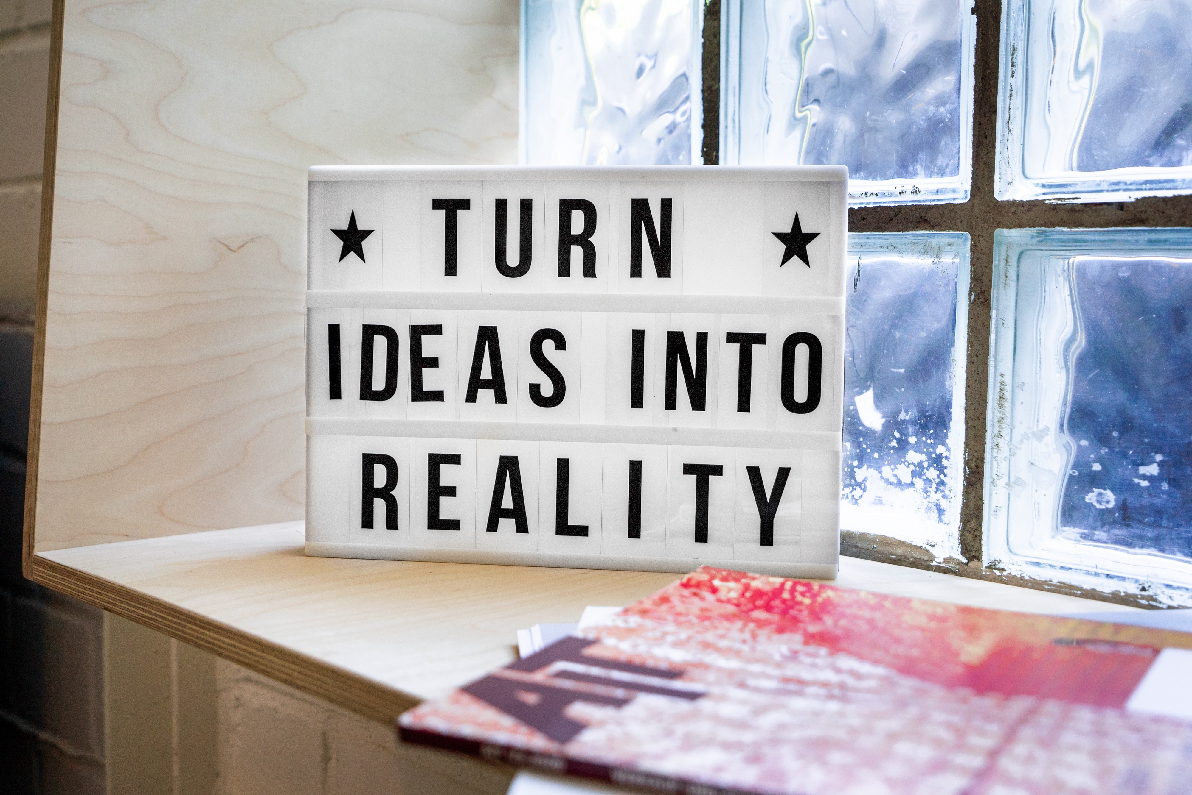 """A white sign on a wooden window sill that says in black letters, """"Turn ideas into reality."""""""