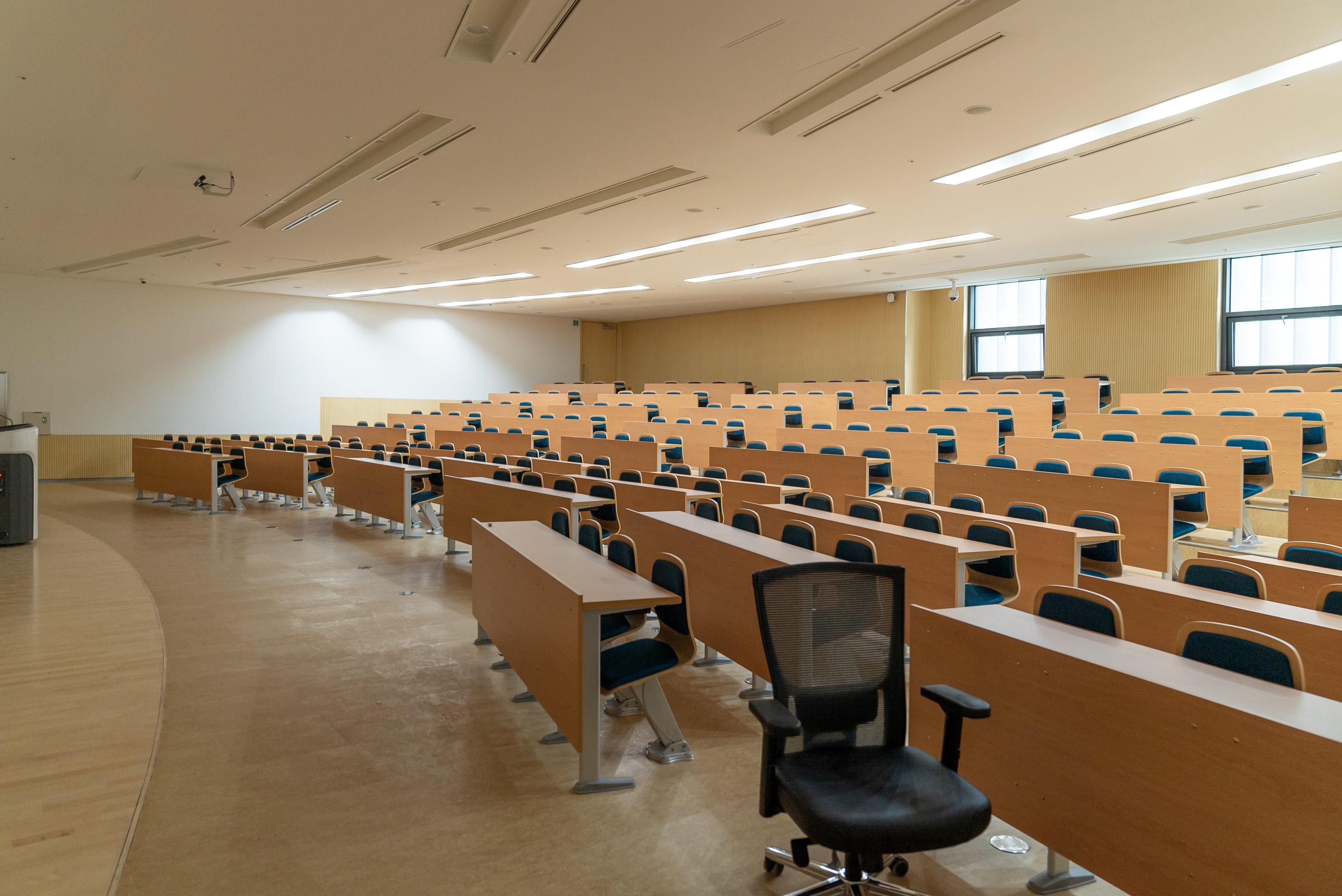 Empty theater style classroom with wooden student chairs and a black swivel intructor's chair