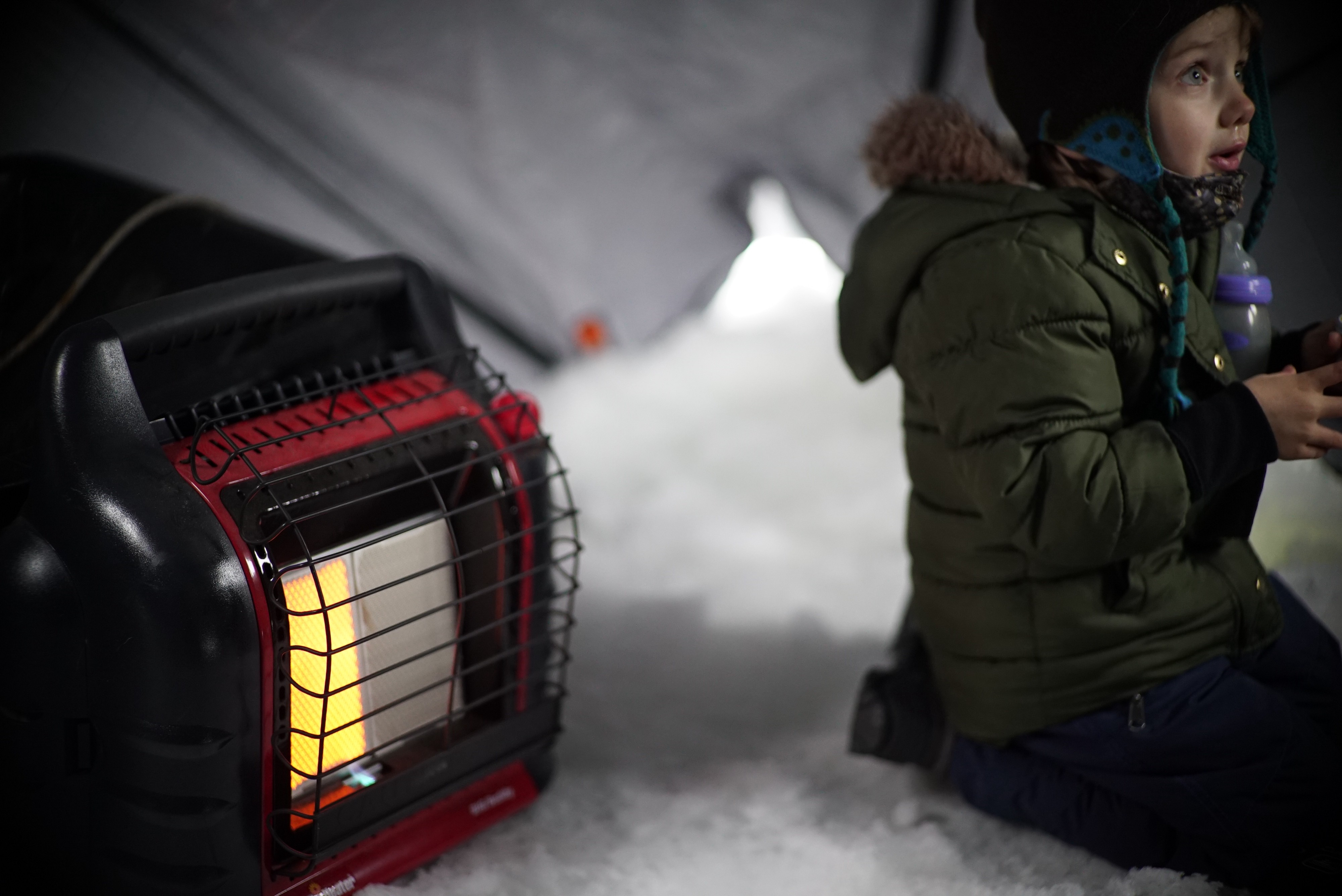 Boy in an ice shack by a portable heater