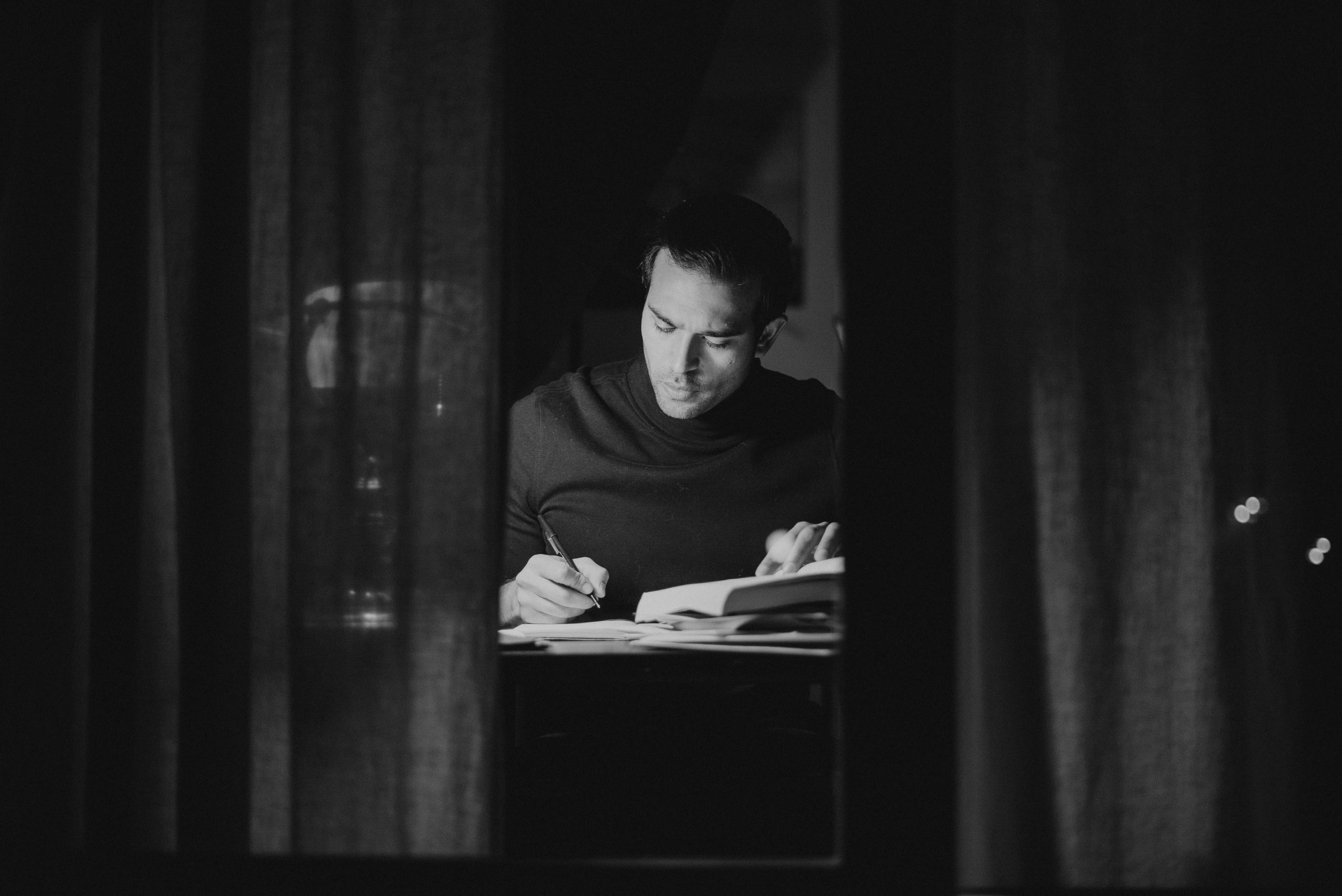 A man writing with a pen while reading.