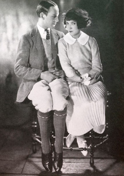 Fred Astaire seated, looking at his sister, Adele, who is looking at the camera.