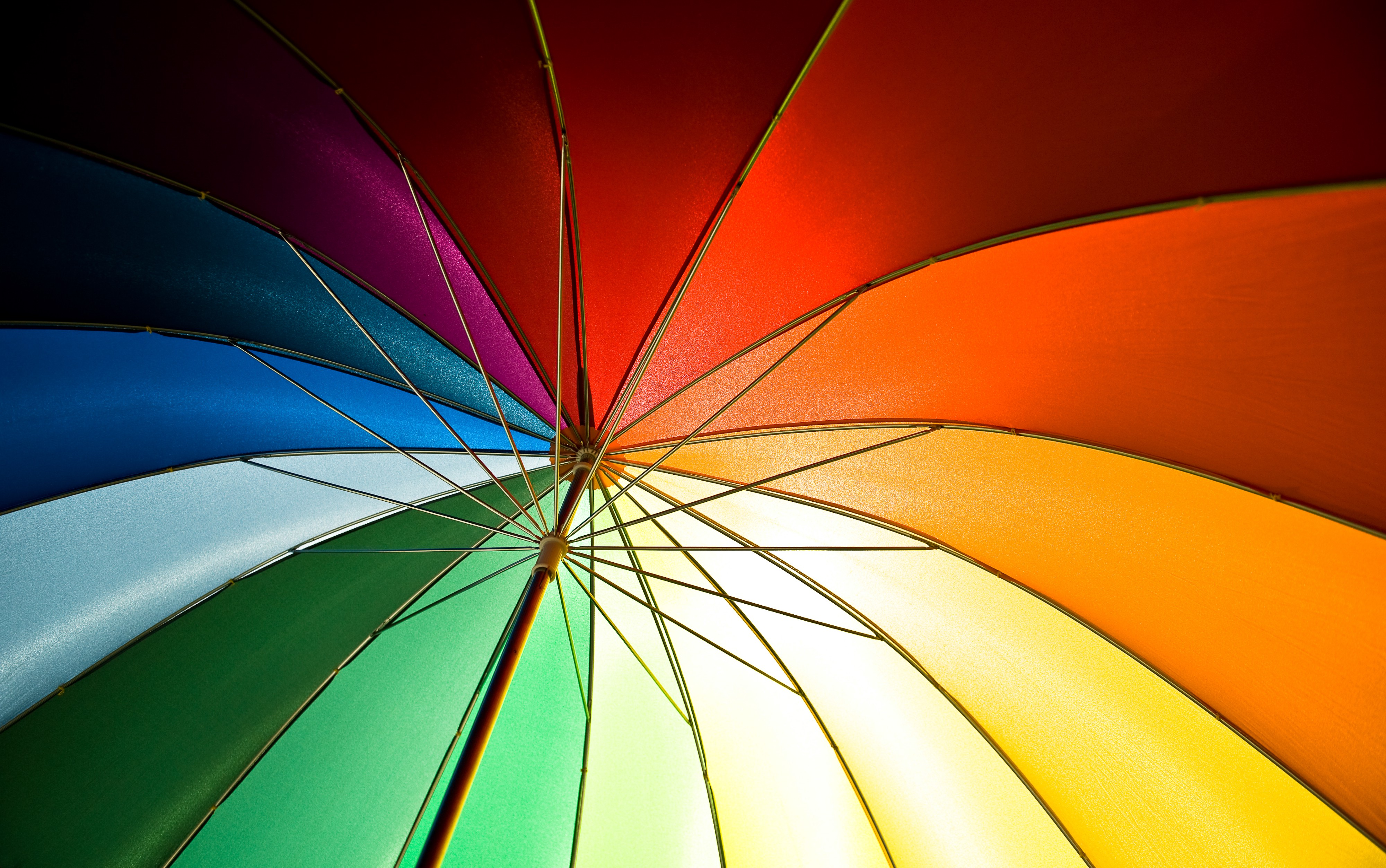 The inside of a rainbow-coloured umbrella, viewed from below