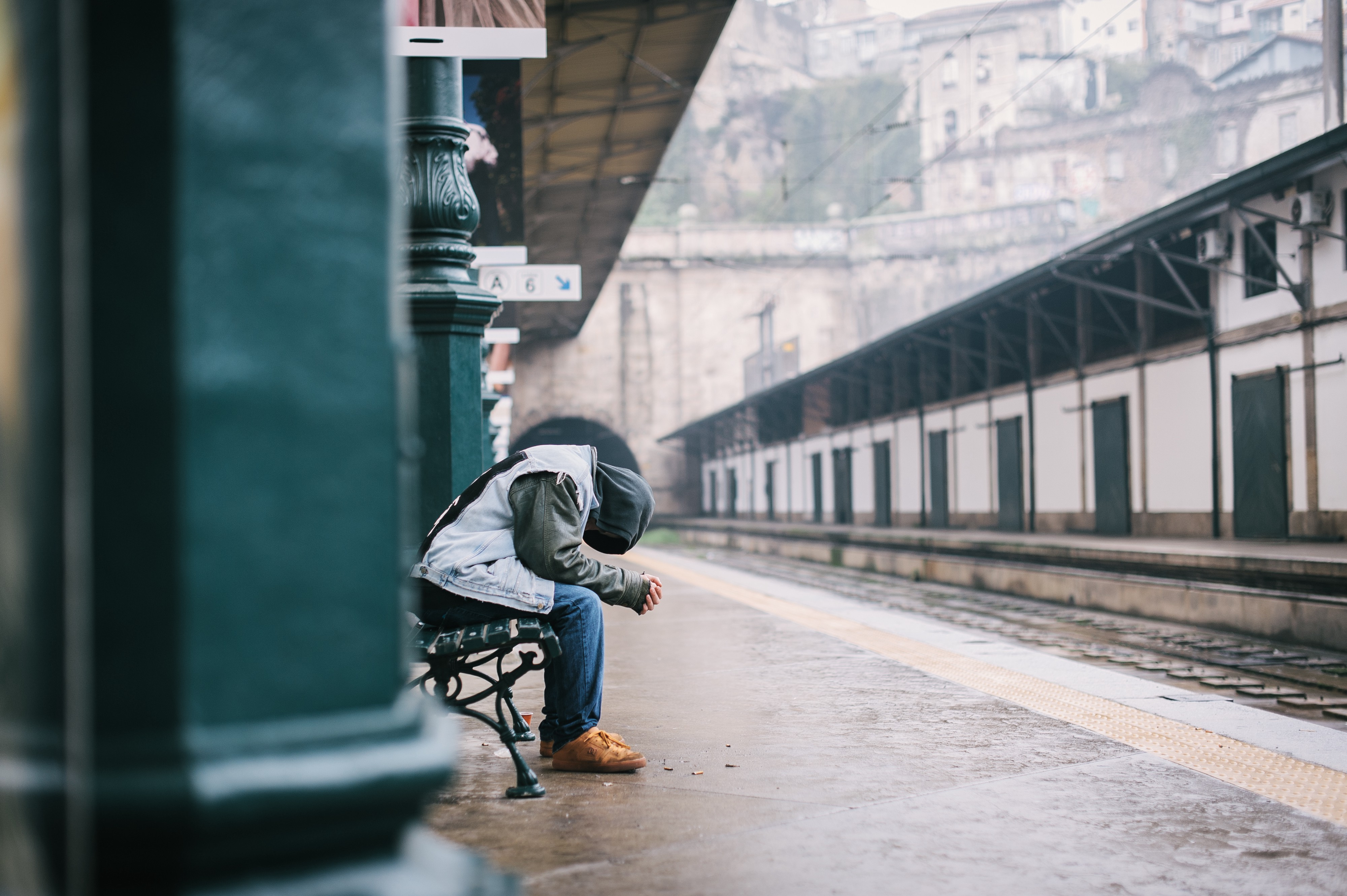 A man at an empty train station with his head bowed in what is presumed to be sadness.