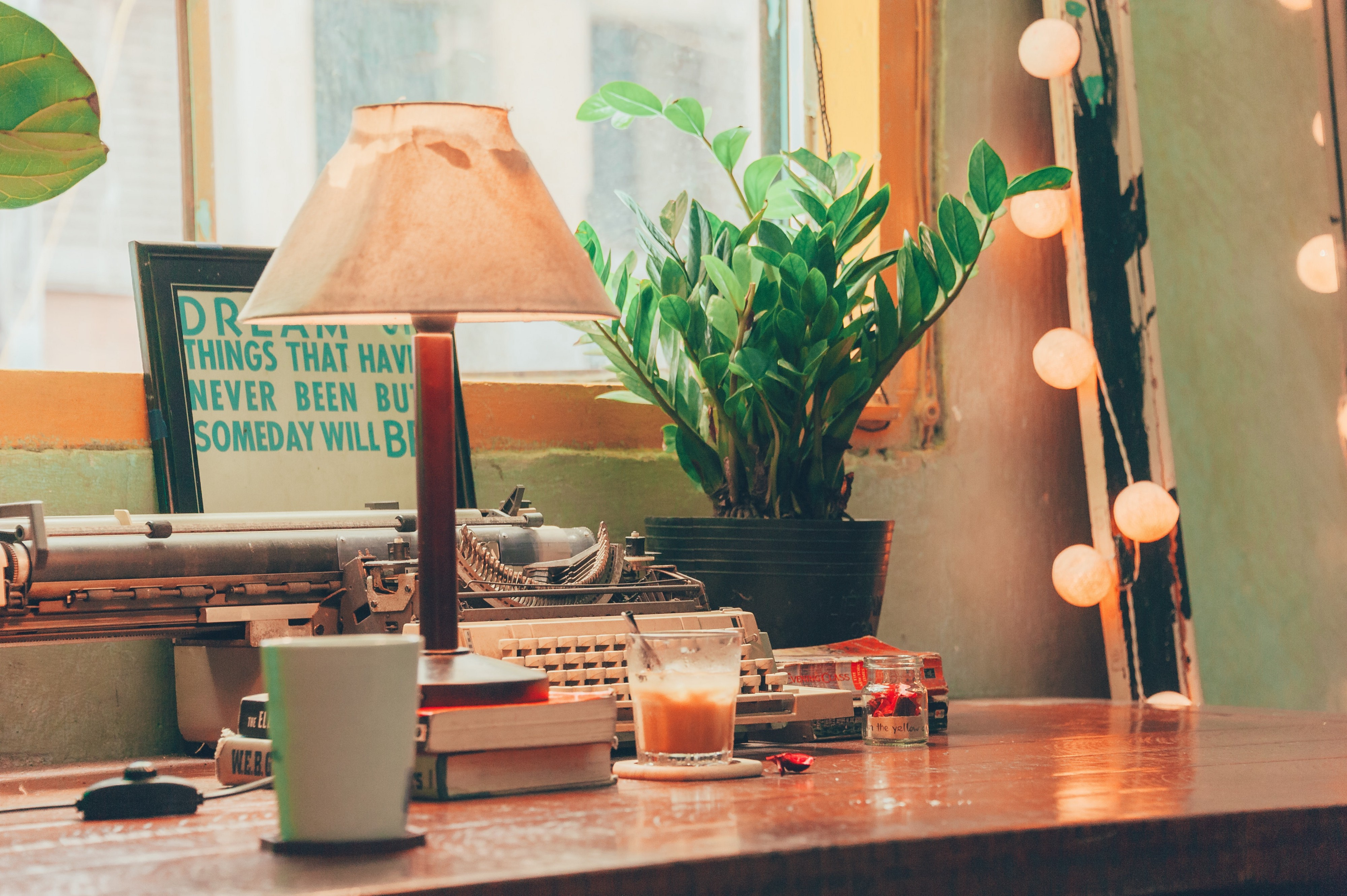 An antique typewriter and a cup of coffee on a wooden desk.