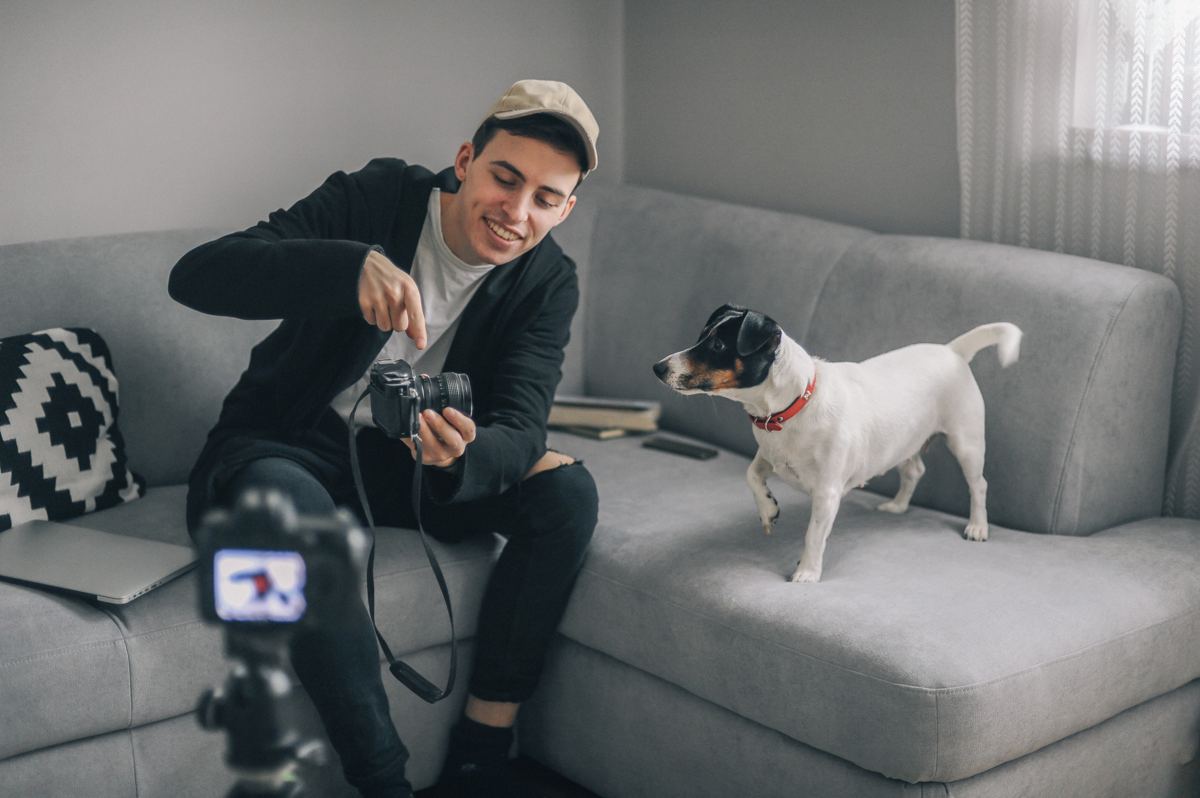 A young man sets up his camera and tripod on his couch. His dog is on the couch looking at him hold his camera.