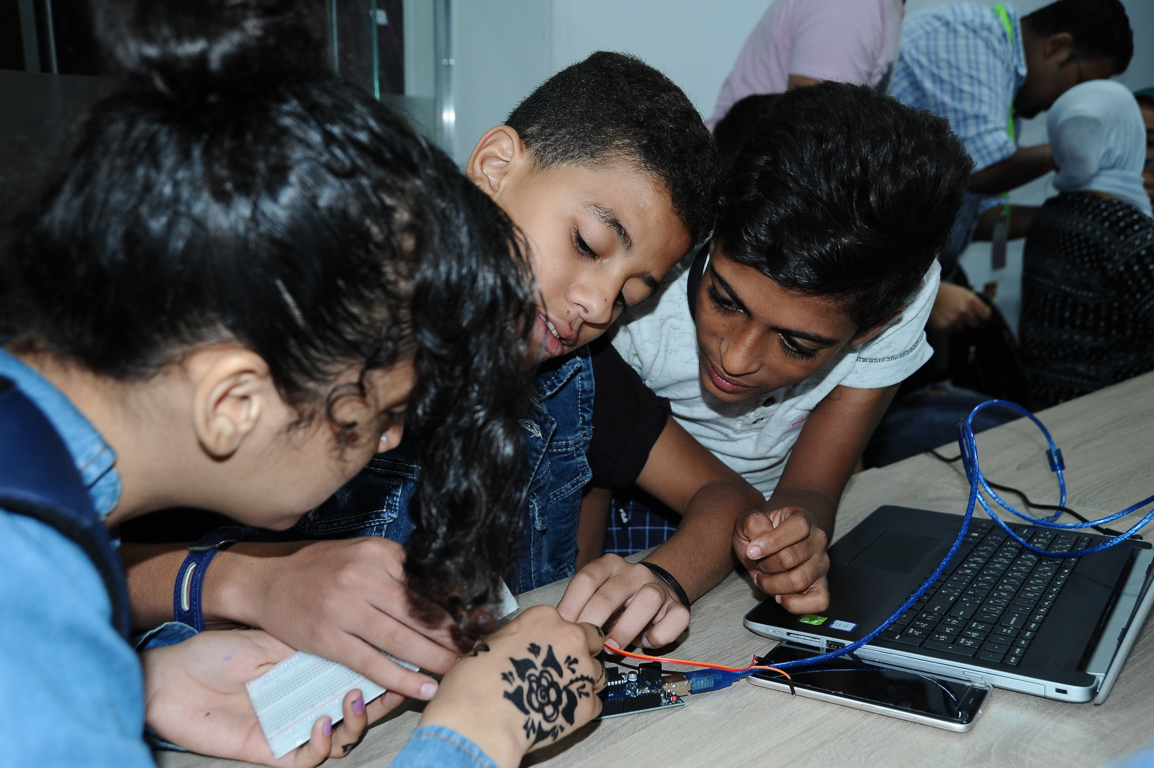 Three students work on a small circuit board.