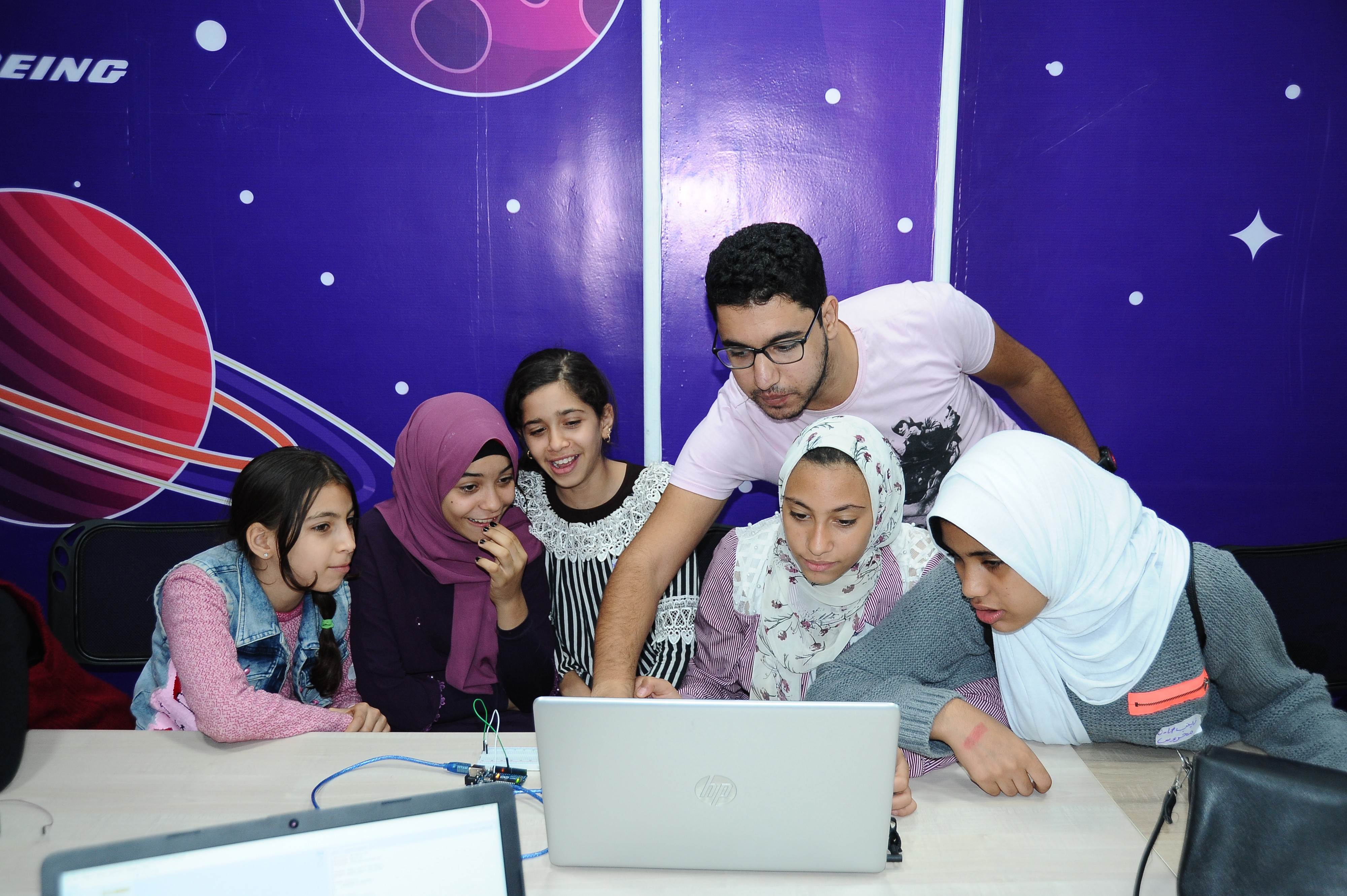 Six students work at a laptop with a mural of the solar system behind them.