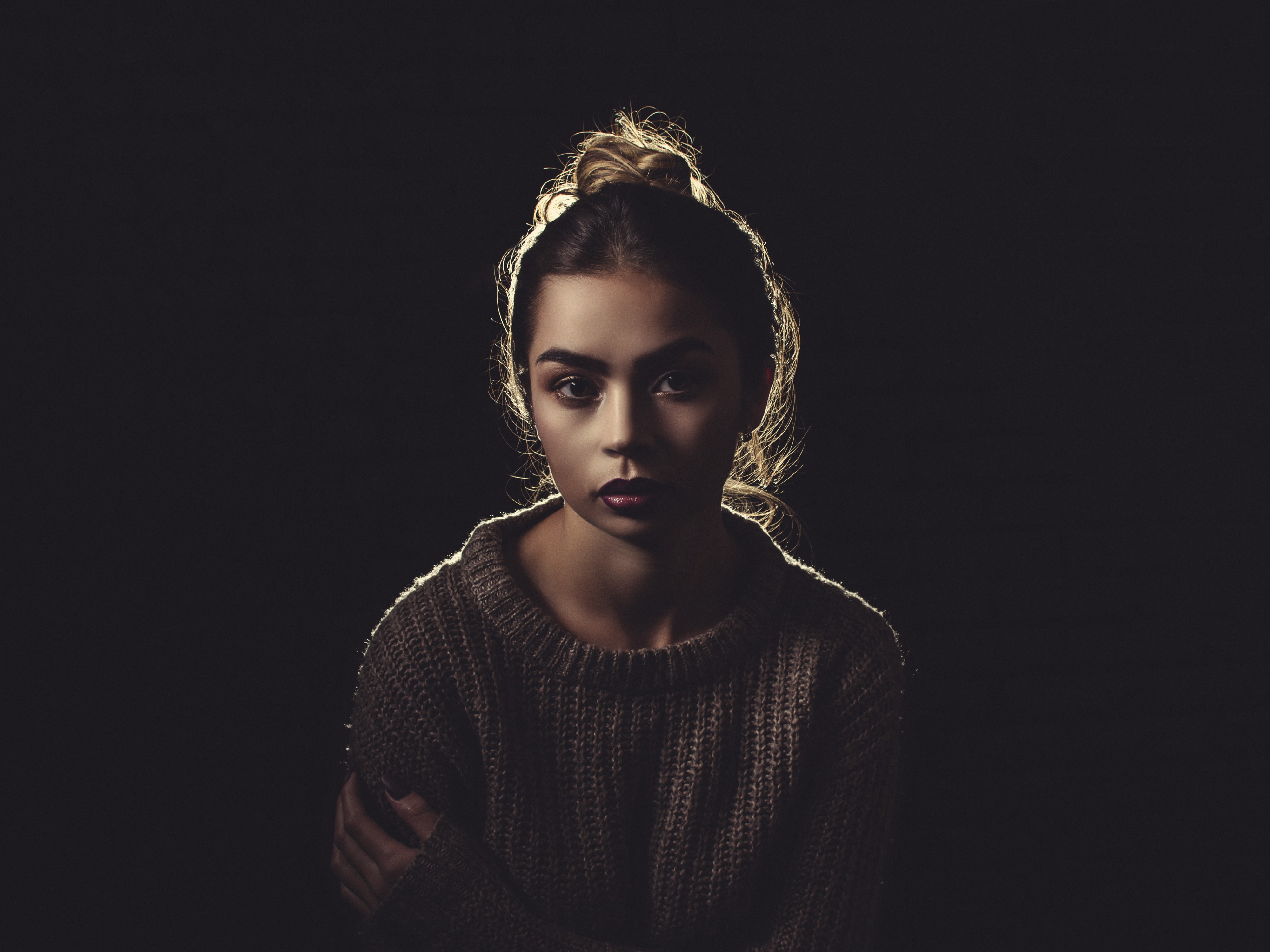 Portrait of a young woman against a black background.