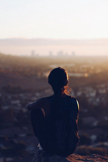 Silhouette of woman sitting with back to camera facing a valley and city skyline.