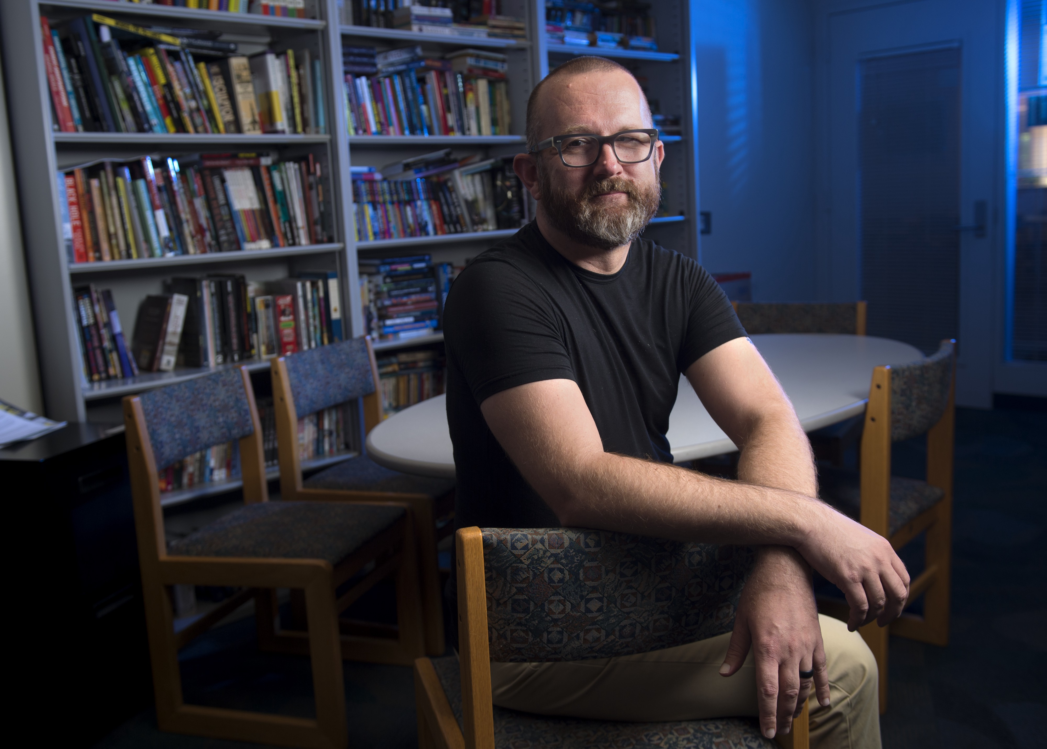 Jonathan Alexander sits in a library, facing the camera