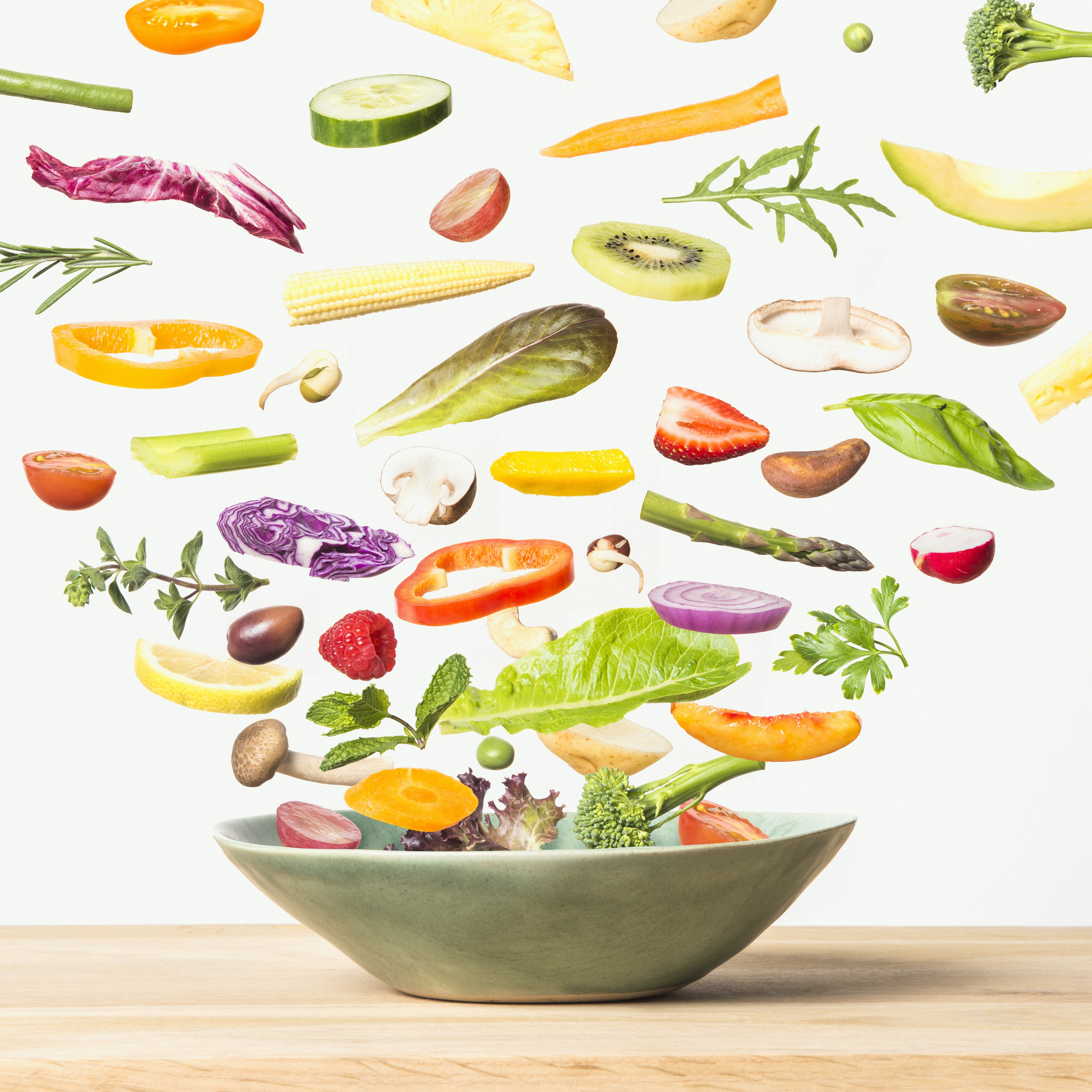 Individual parts of a salad (lettuce, olives, peppers, asparagus, etc) flying out of a salad bowl.
