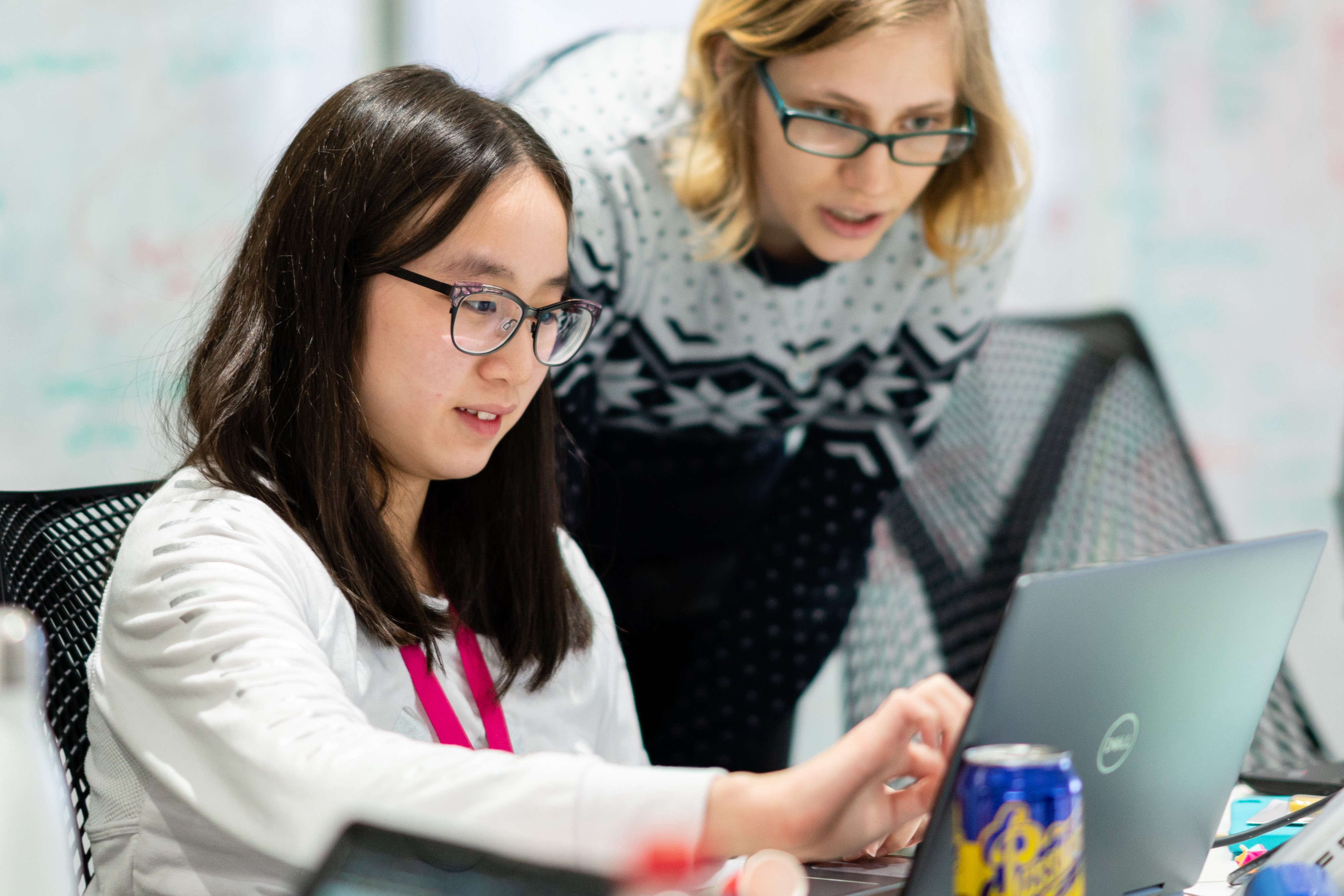 Two young women working together at a laptop