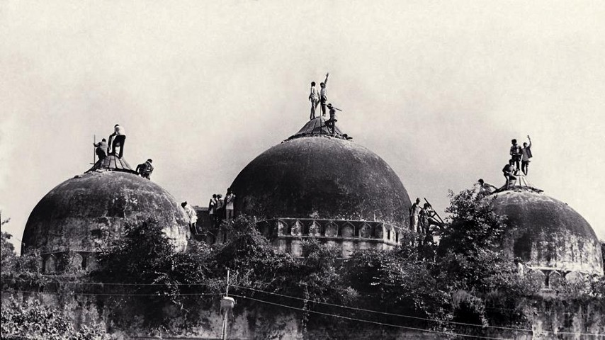 The three domes of Babri Masjid with the some from the mob that will soon demolish the structure climbed on top of it.