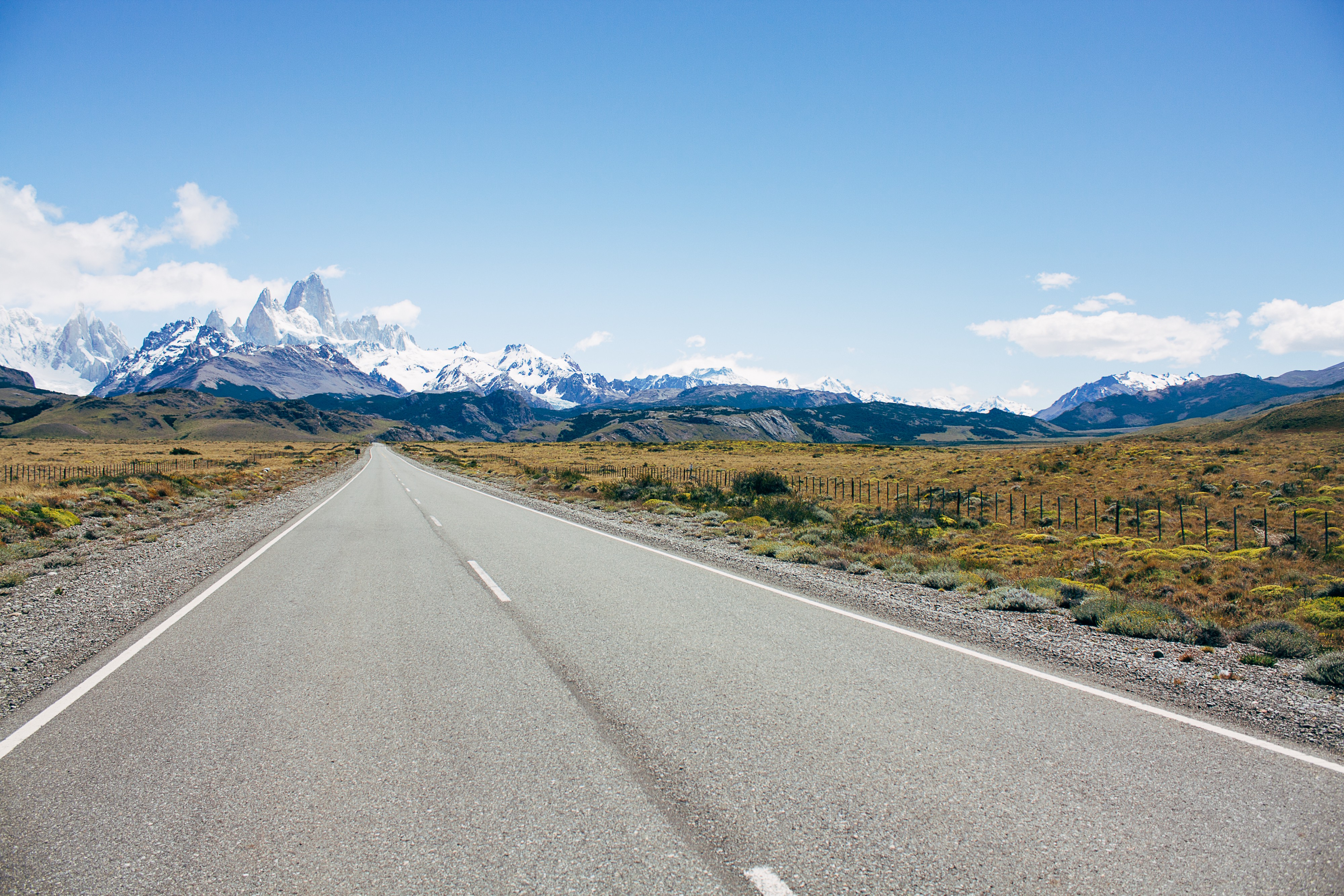 Photo of a long open road with snow=capped mountains in the distance by Ana Viegas.