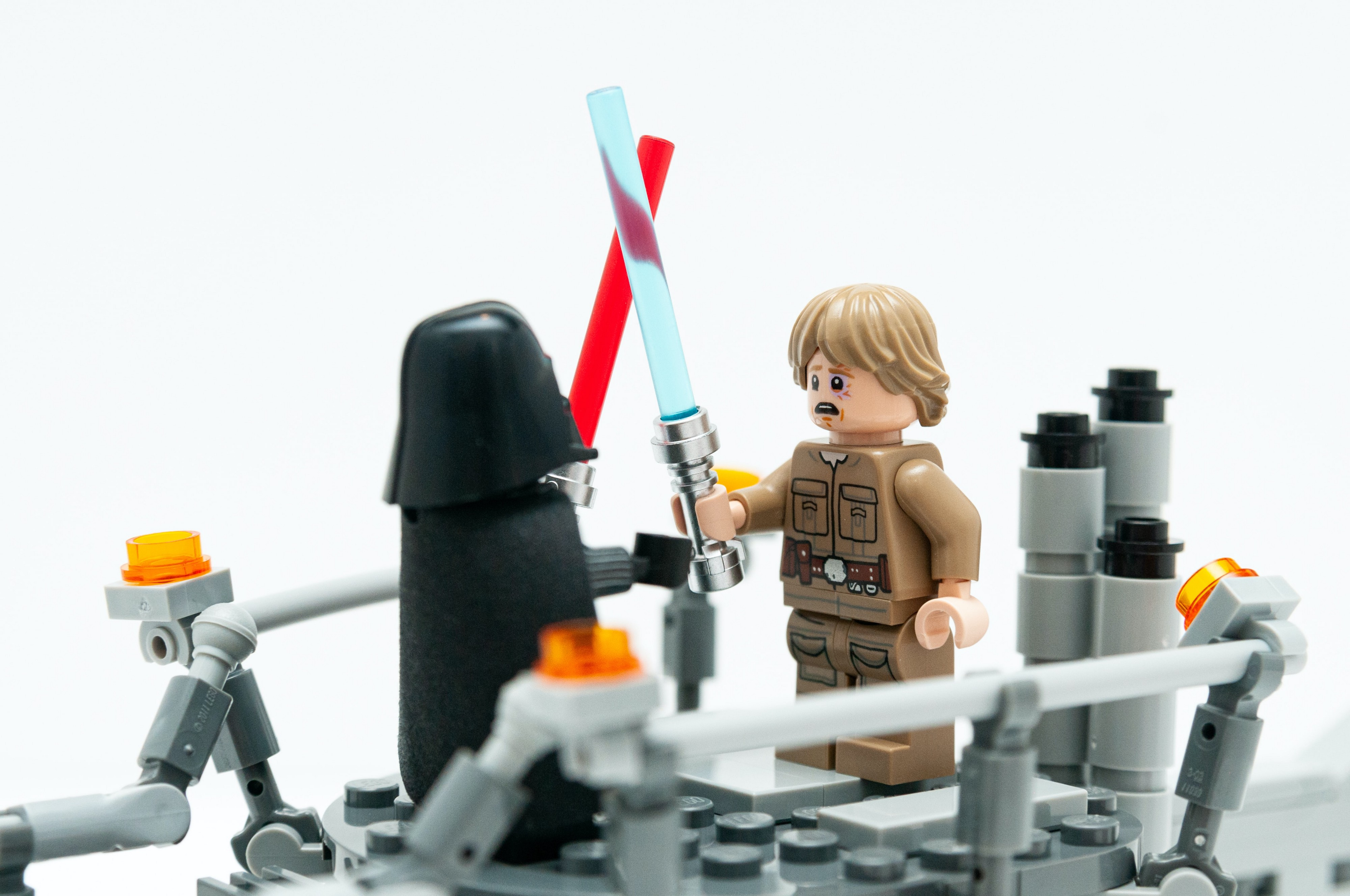 A lego Luke Skywalker fighting a lego Darth Vader with their light sabres. Luke looks unhappy.