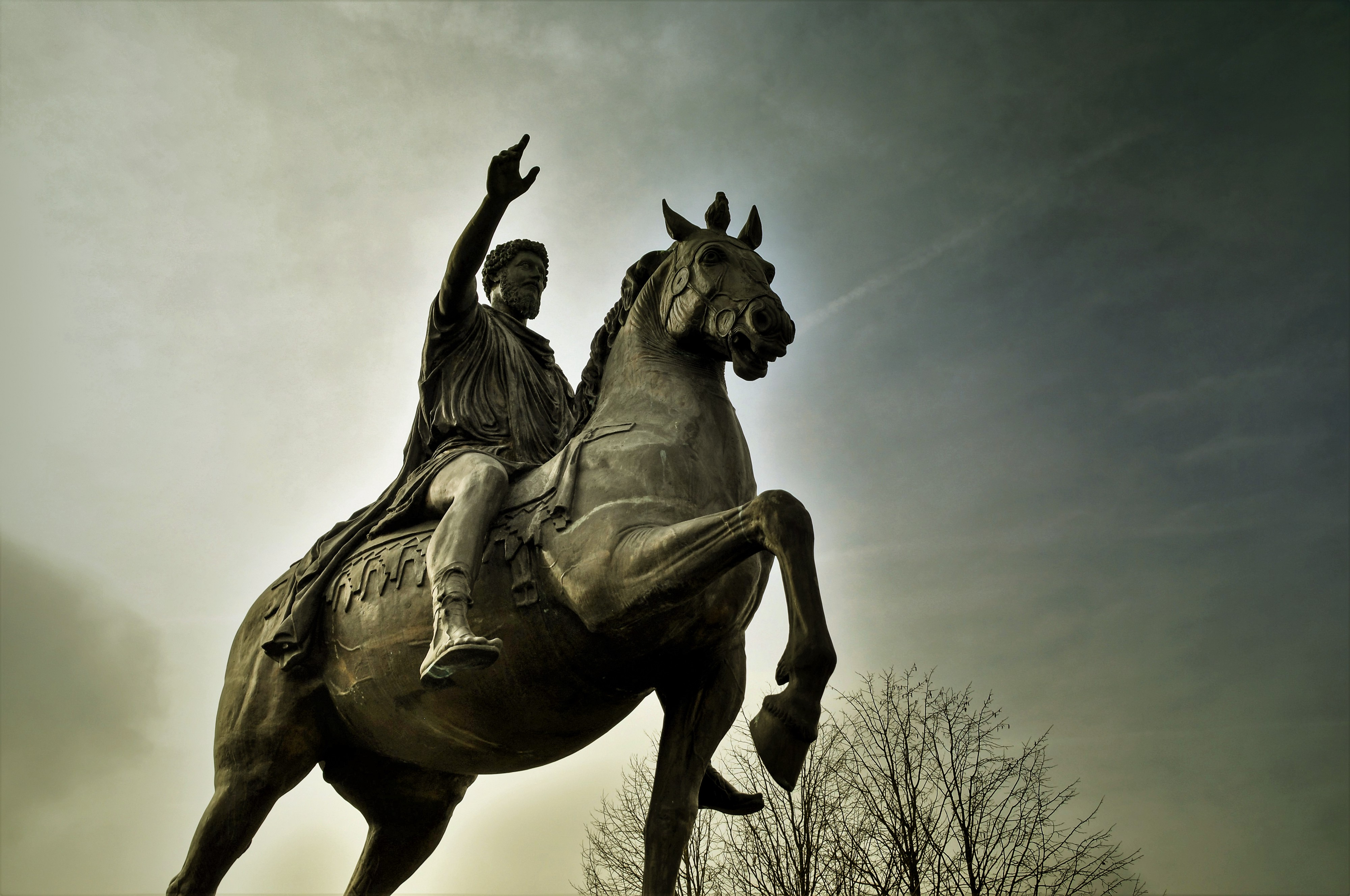 A photo of a sculpture of a man on a horse (presumably a Greek philosopher).
