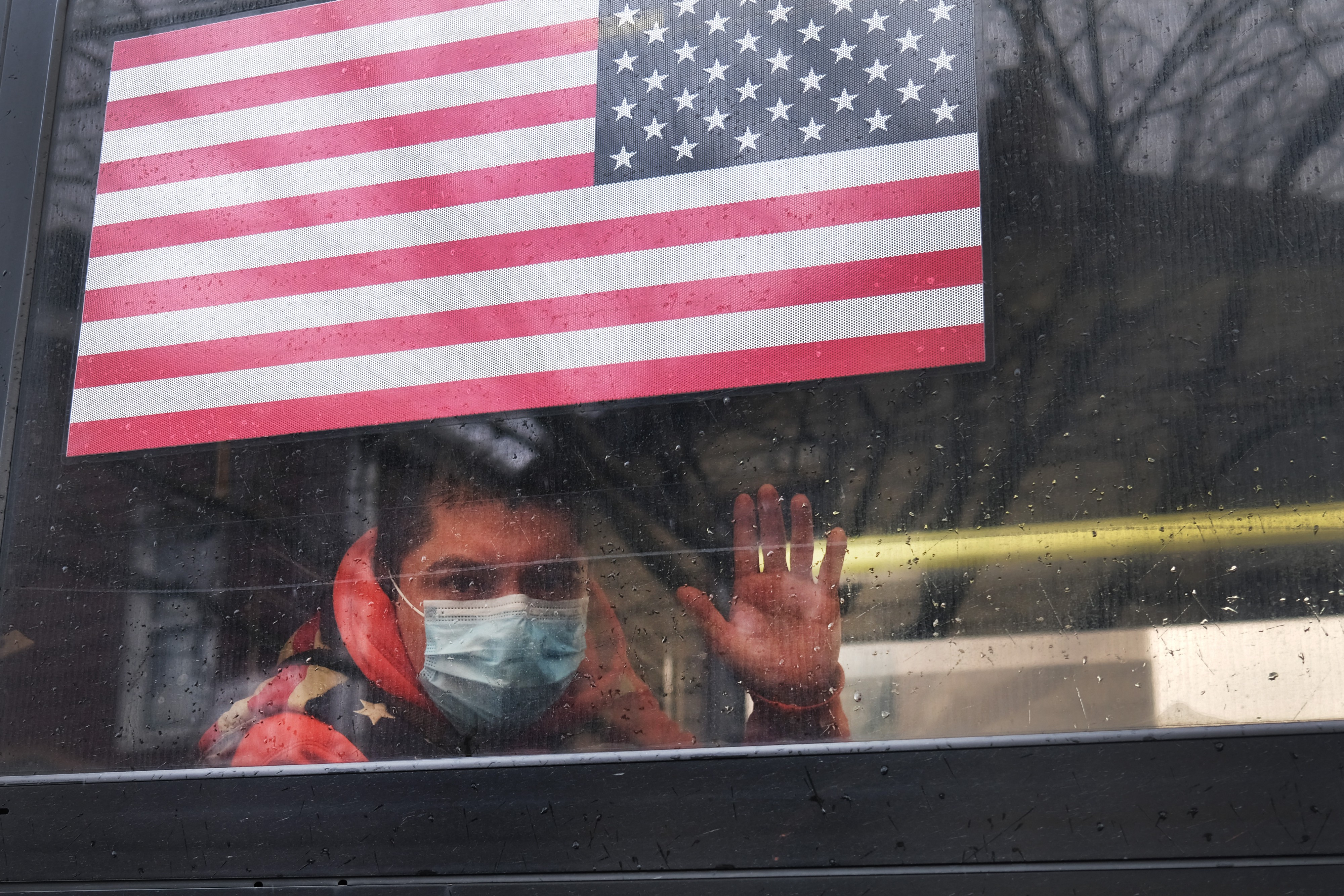 A man waves from a bus in a neighborhood in the Queens borough, which has one of the highest infection rates of coronavirus.