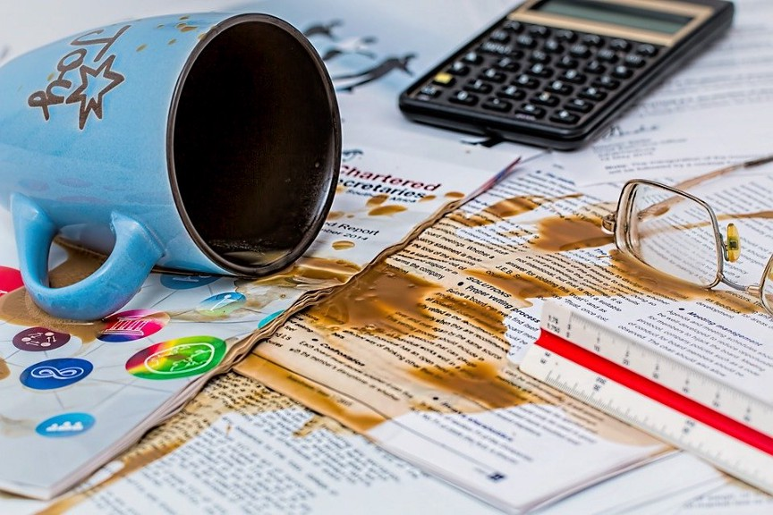Overturned coffee mug and spilled coffee on business papers