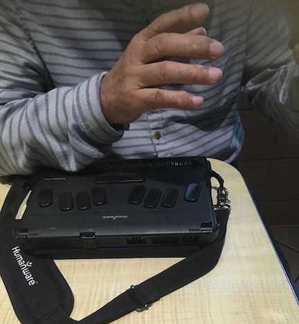 Blind man gesturing over a Humanware electronic braille keyboard