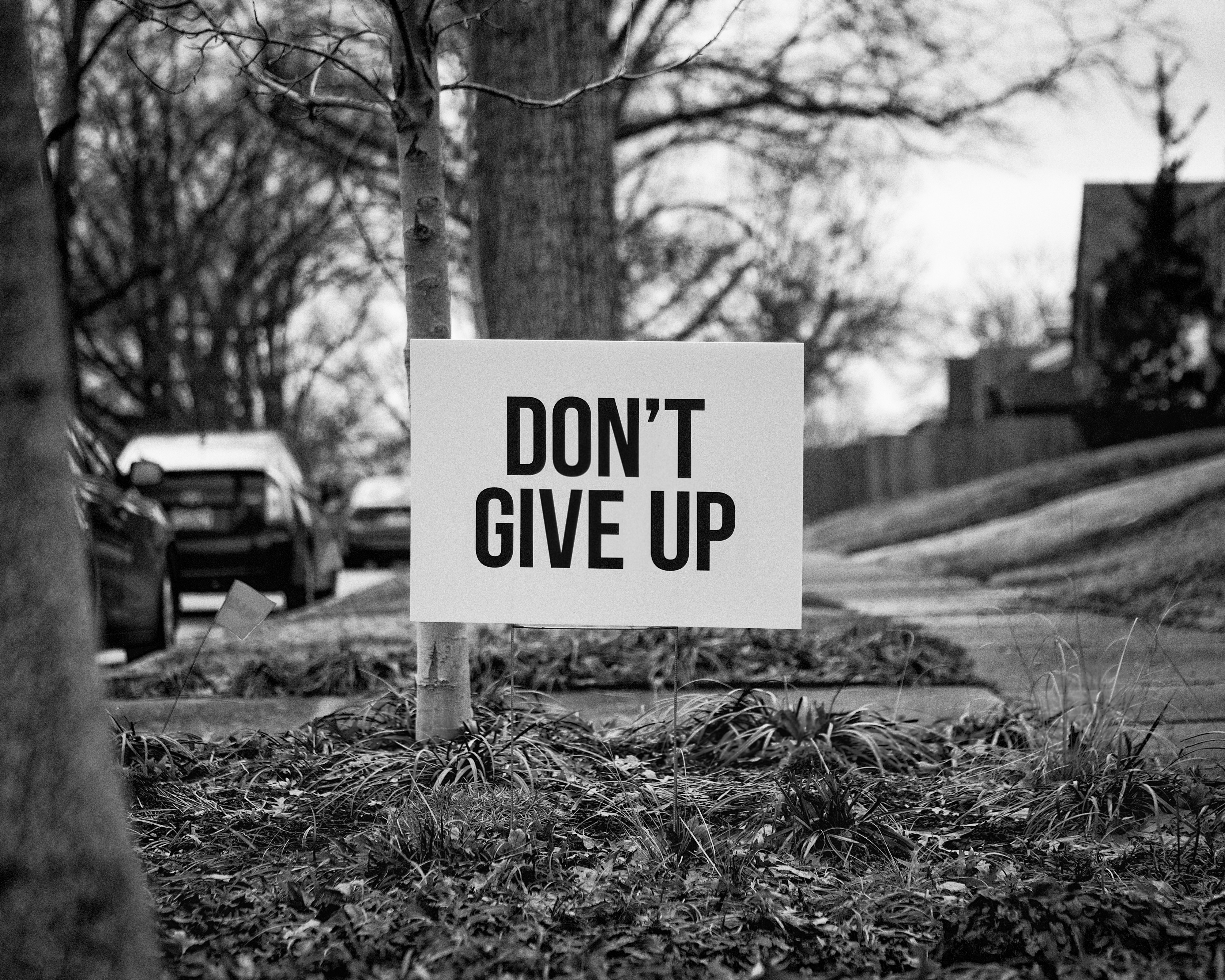 """road sign with the words """"don't give up"""" written on it in black letters"""